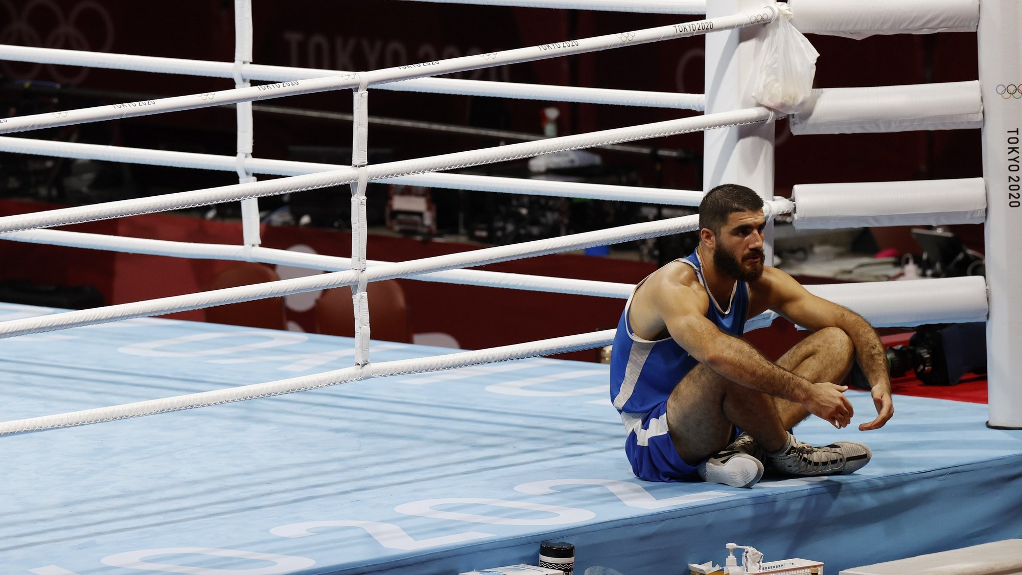 epa09383986 Mourad Aliev of France sits outside the ring in protest after losing his match against Frazer Clarke of Great Britain in the Men's Super Heavy (+91kg) quarterfinal match of the Boxing events of the Tokyo 2020 Olympic Games at the Ryogoku Kokugikan Arena in Tokyo, Japan, 01 August 2021.  EPA/RUNGROJ YONGRIT