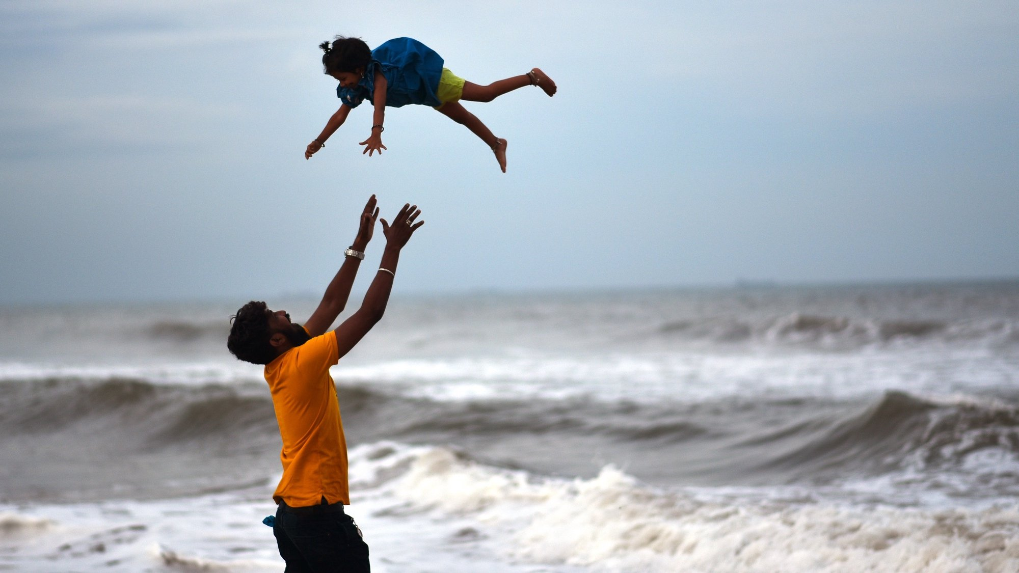 epa09335592 A Indian man throws a child in the air at Marina beach following the ease in Covid-19 lockdown restrictions in Chennai, India, 10 July 2021. Tamil Nadu state government eases ongoing lockdown restrictions following a marginal drop in Covid-19 cases in the state.  EPA/IDREES MOHAMMED