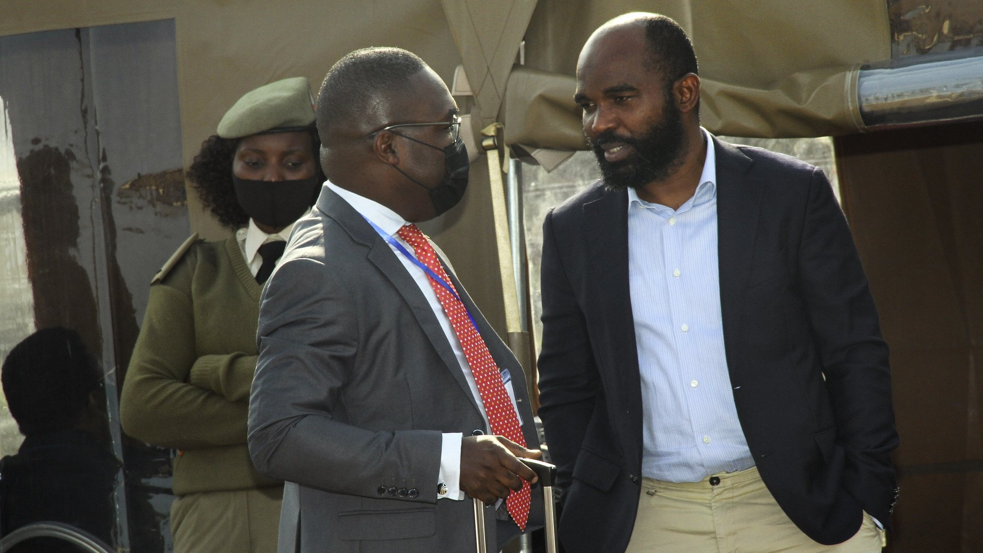 """O réu António Carlos do Rosário (D), diretor de Inteligência Económica do Serviço de Informação e Segurança do Estado (SISE) e ex-PCA das empresas Proindicus, MAM e EMATUM, em conversa com o seu advogado, Alexandre Chivale (E), à porta da sala de sessão do julgamento em Maputo, Moçambique, 23 de agosto de 2021. A defesa de cinco dos 19 arguidos do processo das 'dívidas ocultas' considerou hoje, durante o julgamento que se iniciou na província de Maputo, a acusação """"surreal"""" e """"presunção forçada"""", pedindo a absolvição dos seus constituintes (ACOMPANHA TEXTO DA LUSA). LUCAS MENESES/LUSA"""