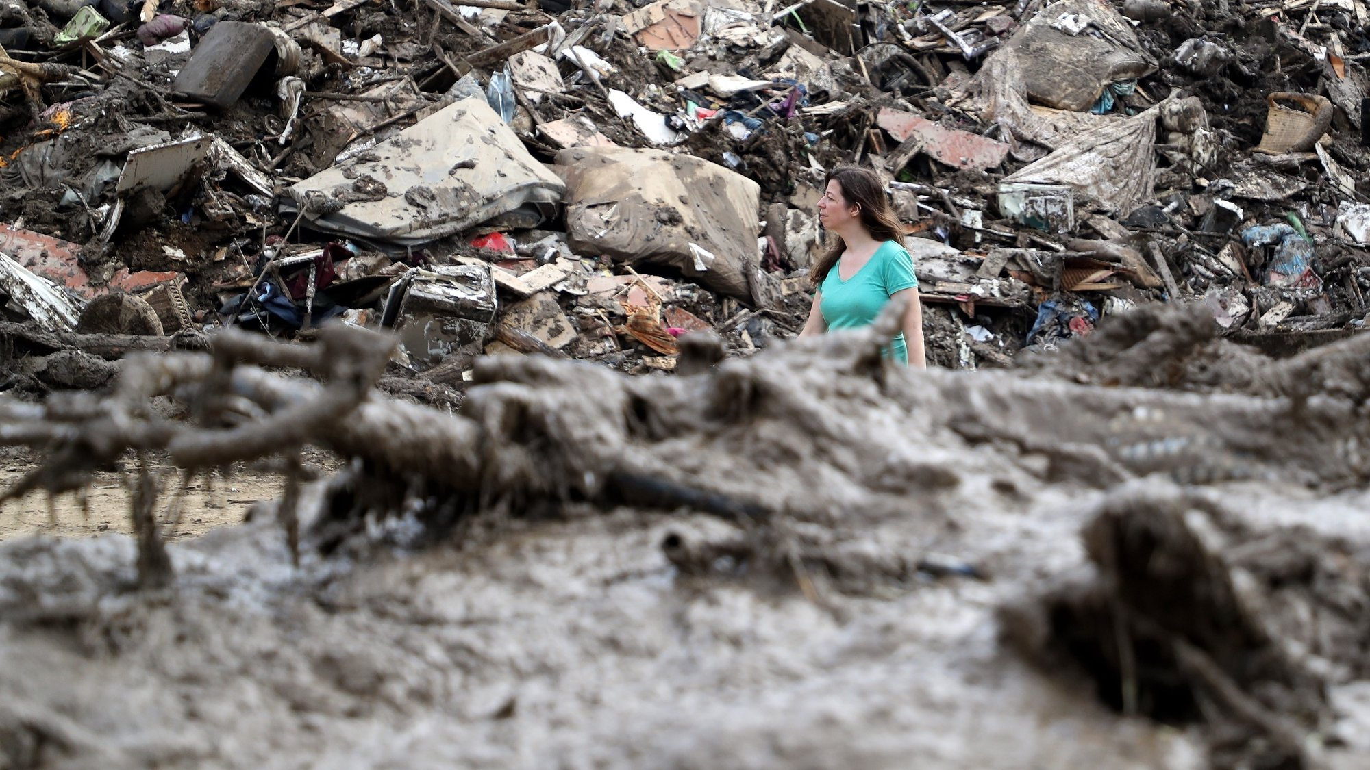 epa09353768 A person walks between the piled up rubbish after the flooding of the Ahr River, in Altenahr, Germany, 19 July 2021. Large parts of western Germany and central Europe were hit by flash floods in the night of 14 to 15 July, following days of continuous rain that destroyed buildings and swept away cars. The total number of victims in the flood disaster in western Germany rises to at least 164, with many hundreds still missing.  EPA/FRIEDEMANN VOGEL