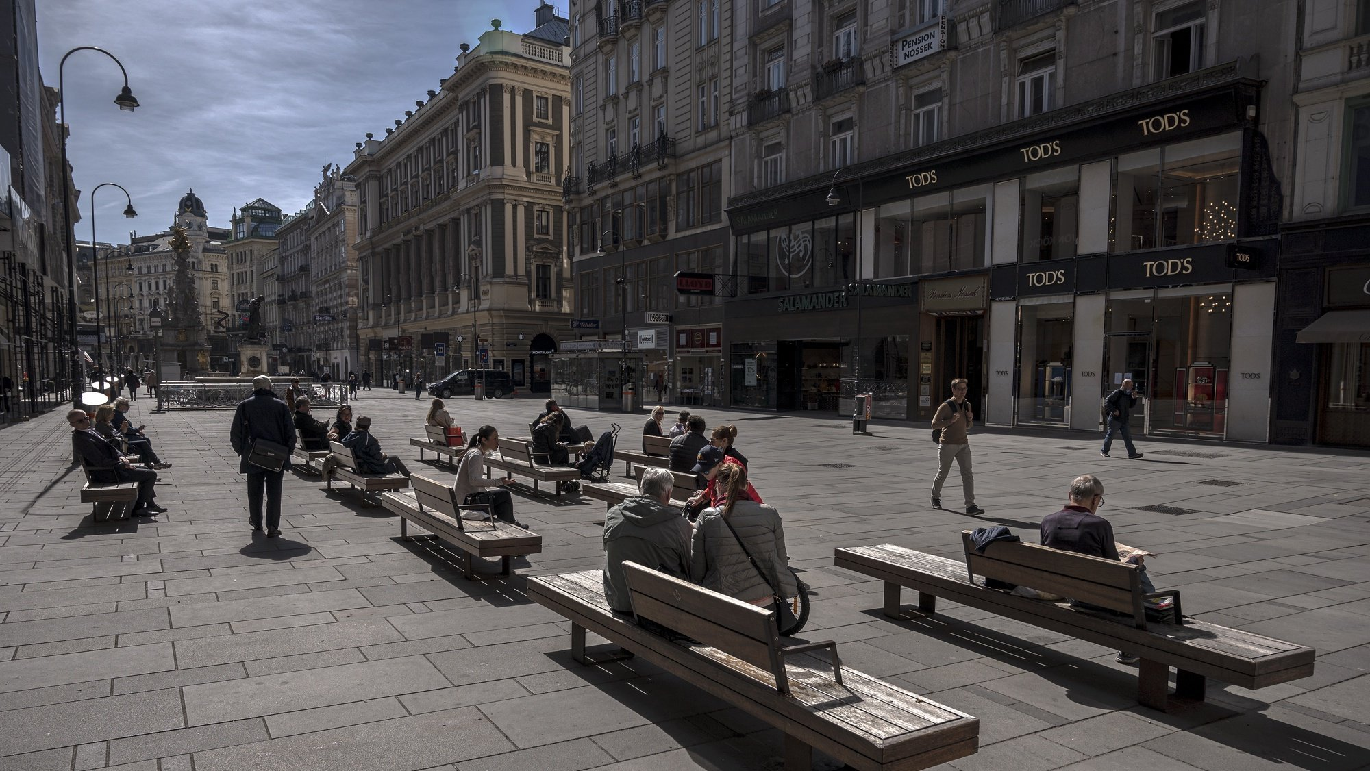 epa08366688 People sit on benches at the Graben shopping street in Vienna, Austria, 16 April 2020. Non essential stores with a shop area under 400 square meters, hardware stores, garden centres and federal parks are allowed to reopen under strict safety measures to slow down the ongoing pandemic of the COVID-19 disease caused by the SARS-CoV-2 coronavirus since 14 April 2020. The government has ordered to wear face masks in supermarkets, pharmacies, various kind of opened shops, public transportation and car pools.  EPA/CHRISTIAN BRUNA