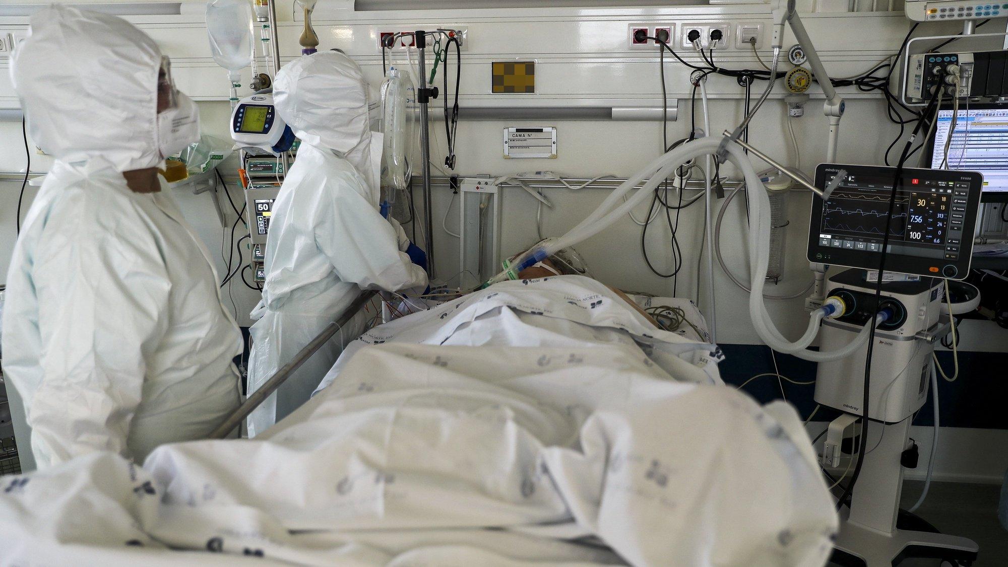 Dois elementos da equipa médica cuidam de uma paciente hospitalizado na Unidade de Cuidados Intensivos covid-19