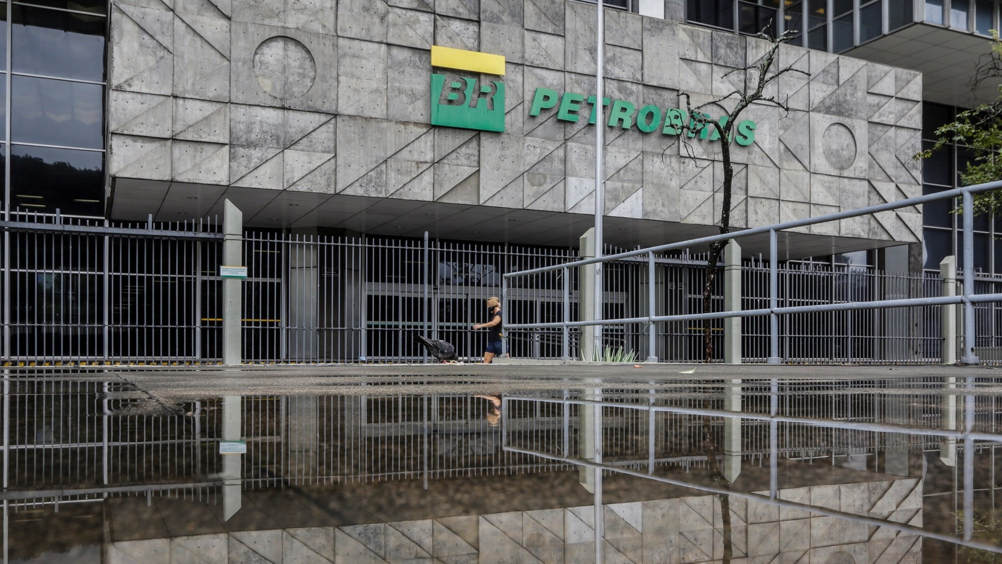 epa09030272 A person walks in front of the Petrobras headquarters in Rio de Janeiro, Brazil, 22 February 2021. The Brazilian president has opened a new crisis in Petrobras by announcing a retired Army general as the new president of the state oil company, which sank in the stock market, and raised doubts about his commitment to economic liberalism.  EPA/Antonio Lacerda