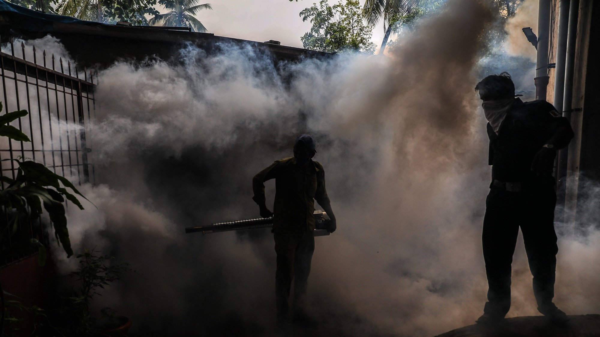 epa08570594 A municipal worker wearing a face mask uses an anti-malaria fumigation spray machine at a residential area in Mumbai, India, 28 July, 2020. The measure is regularly taken by the municipal corporation to try to avoid any kind of diseases caused by mosquitoes. The workers, reportedly, fumigate in all areas of the city, from slum to high rise residential buildings, from shops to sewage canals, ponds and puddles in the streets.  EPA/DIVYAKANT SOLANKI