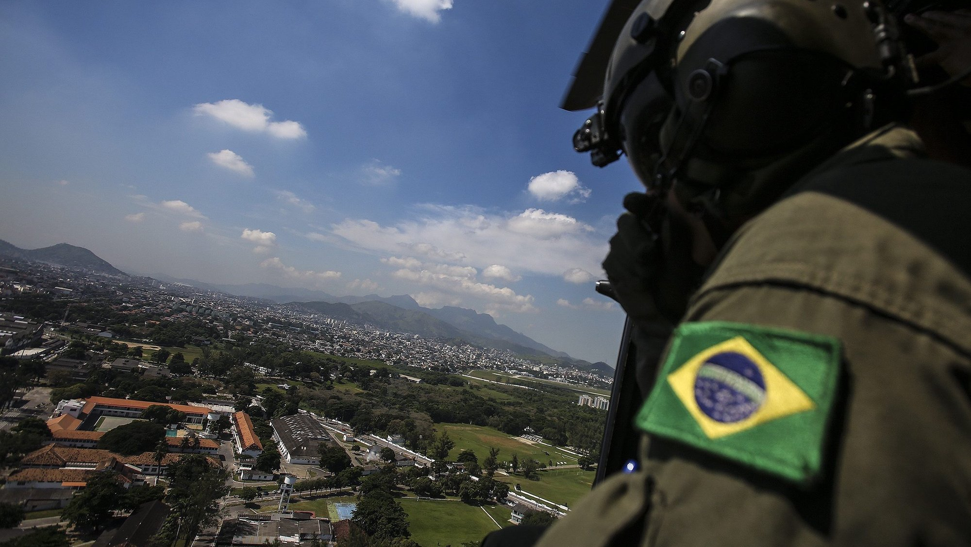 epa05246706 Brazilian Air Force soldiers fly over the neighborhood of Deodoro, venue for several Olympic events, as part of the operation 'Pao de Acucar' ('Sugar Loaf') security preparations for the 2016 Rio Olympics, in Rio de Janeiro, Brazil, 06 April 2016.  EPA/Antonio Lacerda