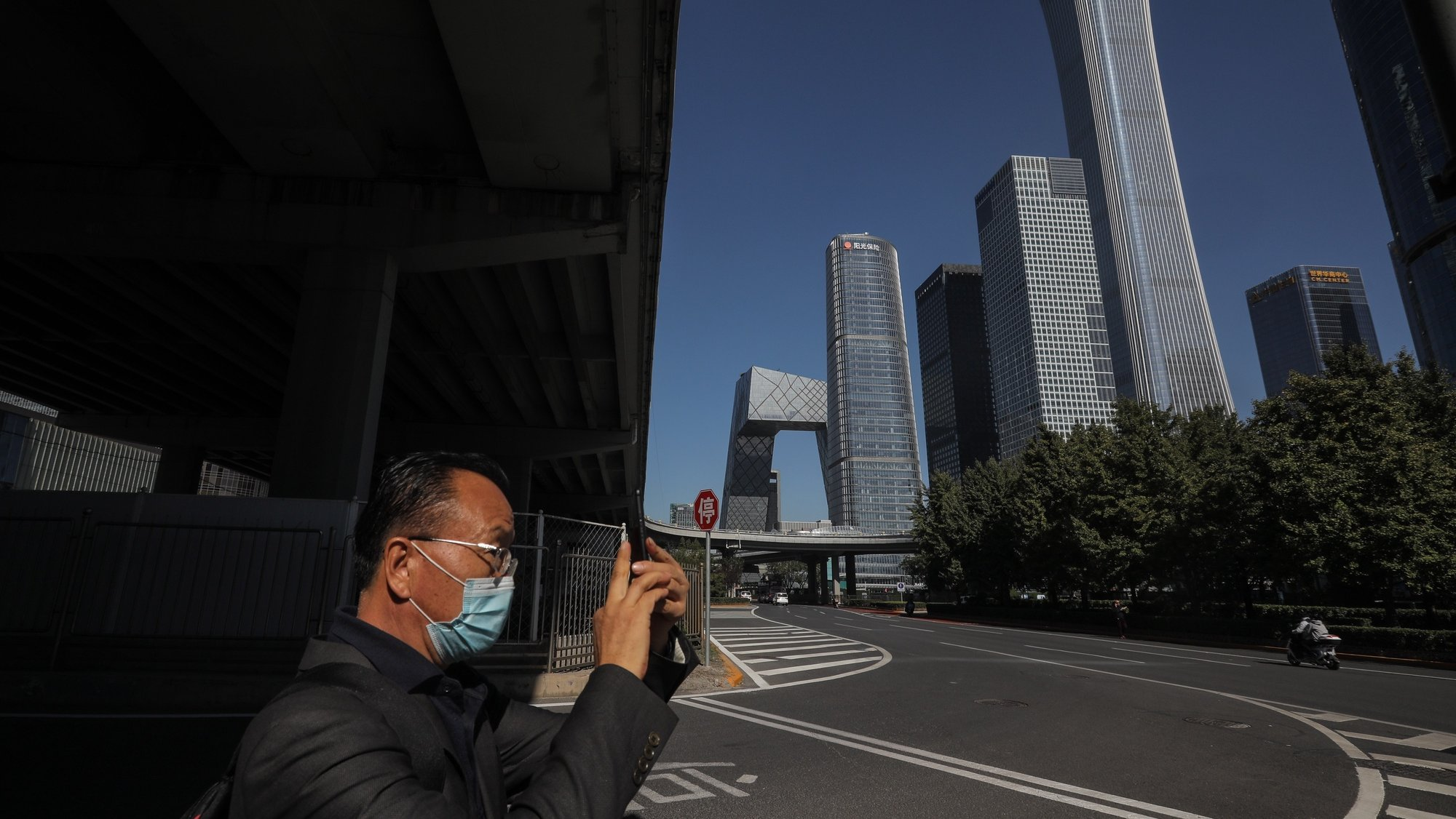 epa09529478 A man uses his mobile phone to take photos in the central business district (CBD) in Beijing, China, 17 October 2021 (issued 18 October 2021). China's gross domestic product (GDP) rose 4.9 percent year on year in the third quarter of 2021, according to data from the National Bureau of Statistics (NBS) issued on 18 October 2021.  EPA/WU HONG