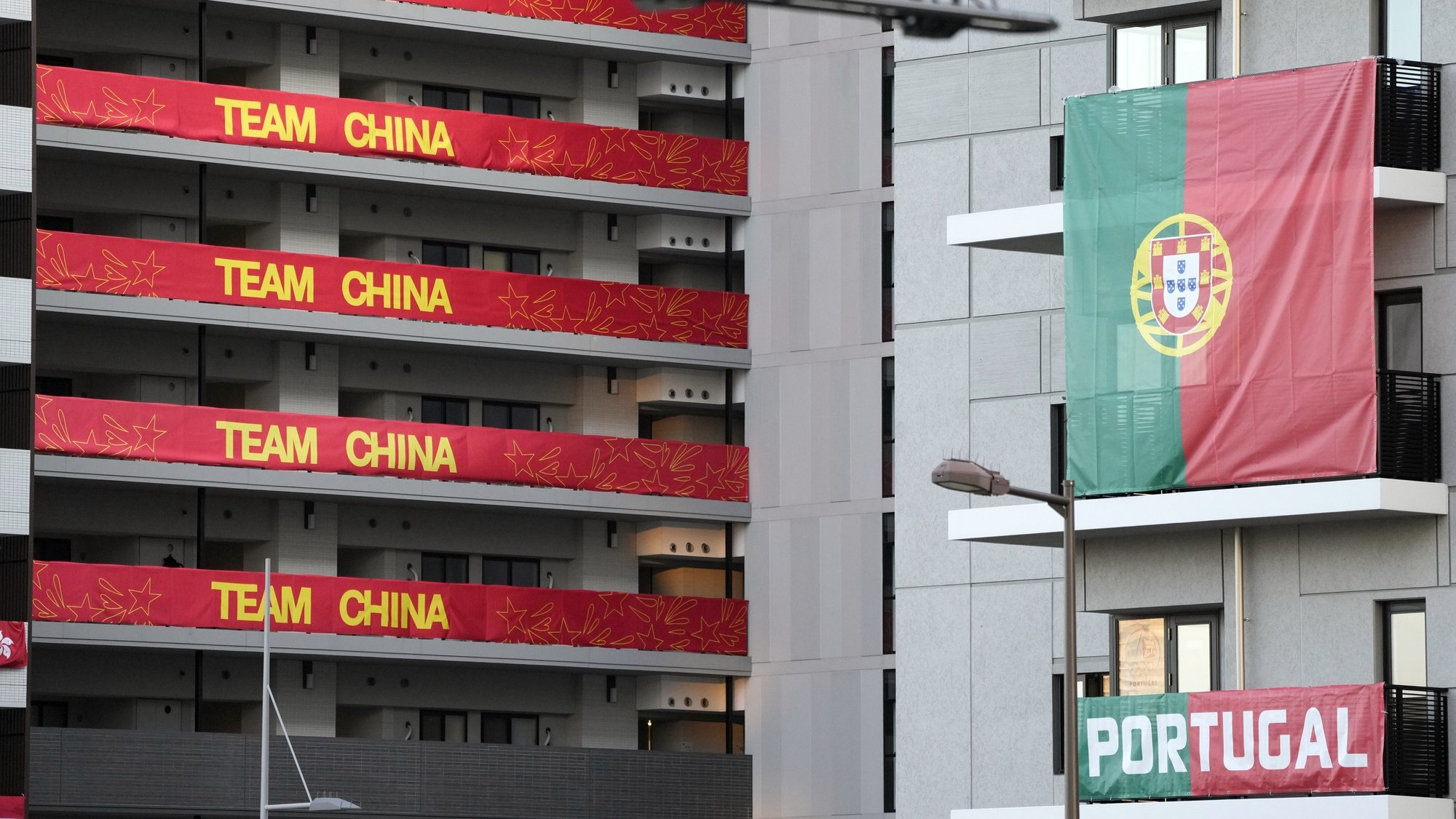 epa09353296 Flags from the Portuguese Olympic team are displayed on buildings hosting Olympic Games participants at the Olympic Village in Tokyo, Japan, 19 July 2021. Just few days before the opening of the Tokyo Games, the Tokyo Olympic Games organizing committee said that 21 people have been certified as close contacts of the three South African men's national soccer team players who have tested positive for COVID-19 and stayed in the Olympic Village.  EPA/FRANCK ROBICHON