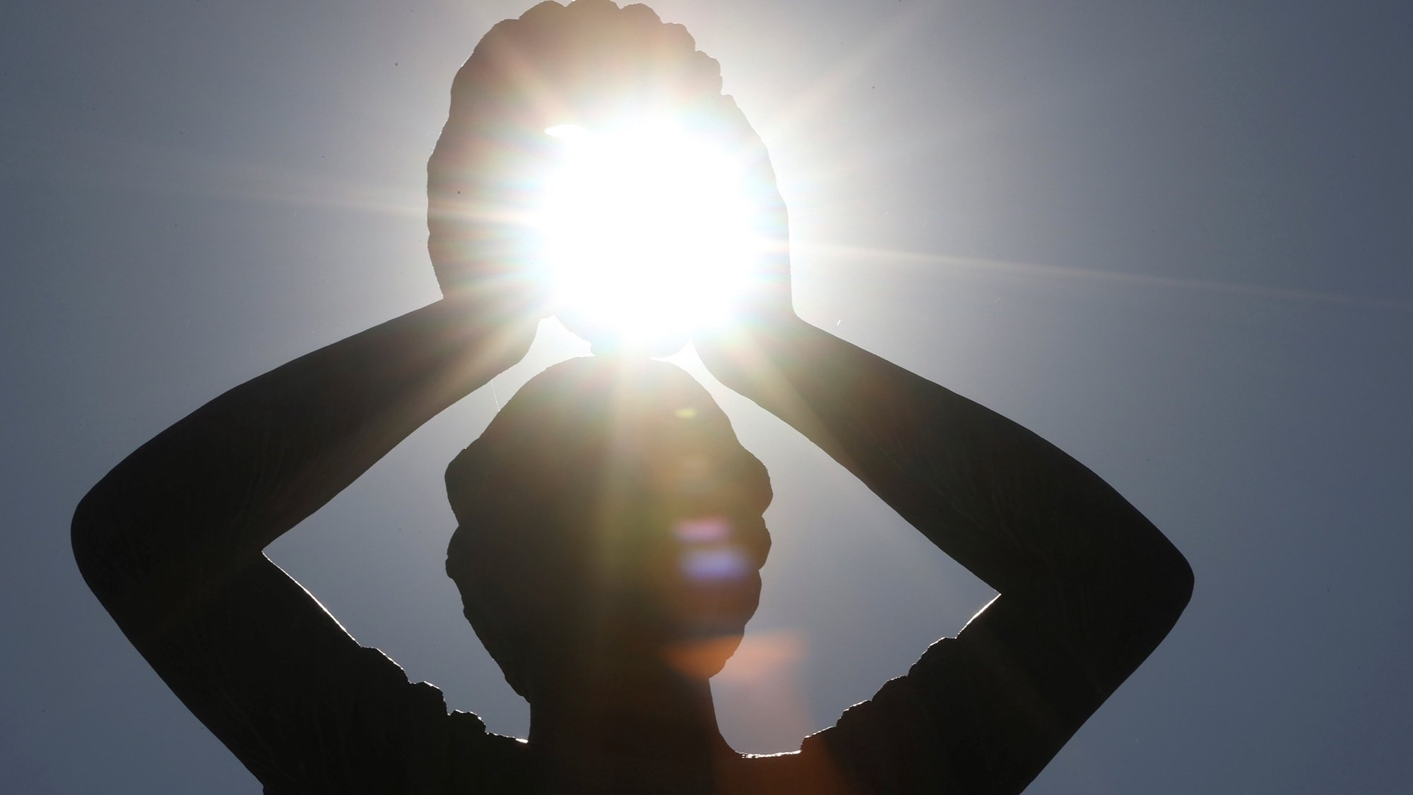 epa08578479 The sun is seen between the hands of a sculpture at Retiro Park in Madrid, Spain, 01 August 2020, during the heat wave that brought temperatures of over 40 degrees Celsius.  EPA/Mariscal