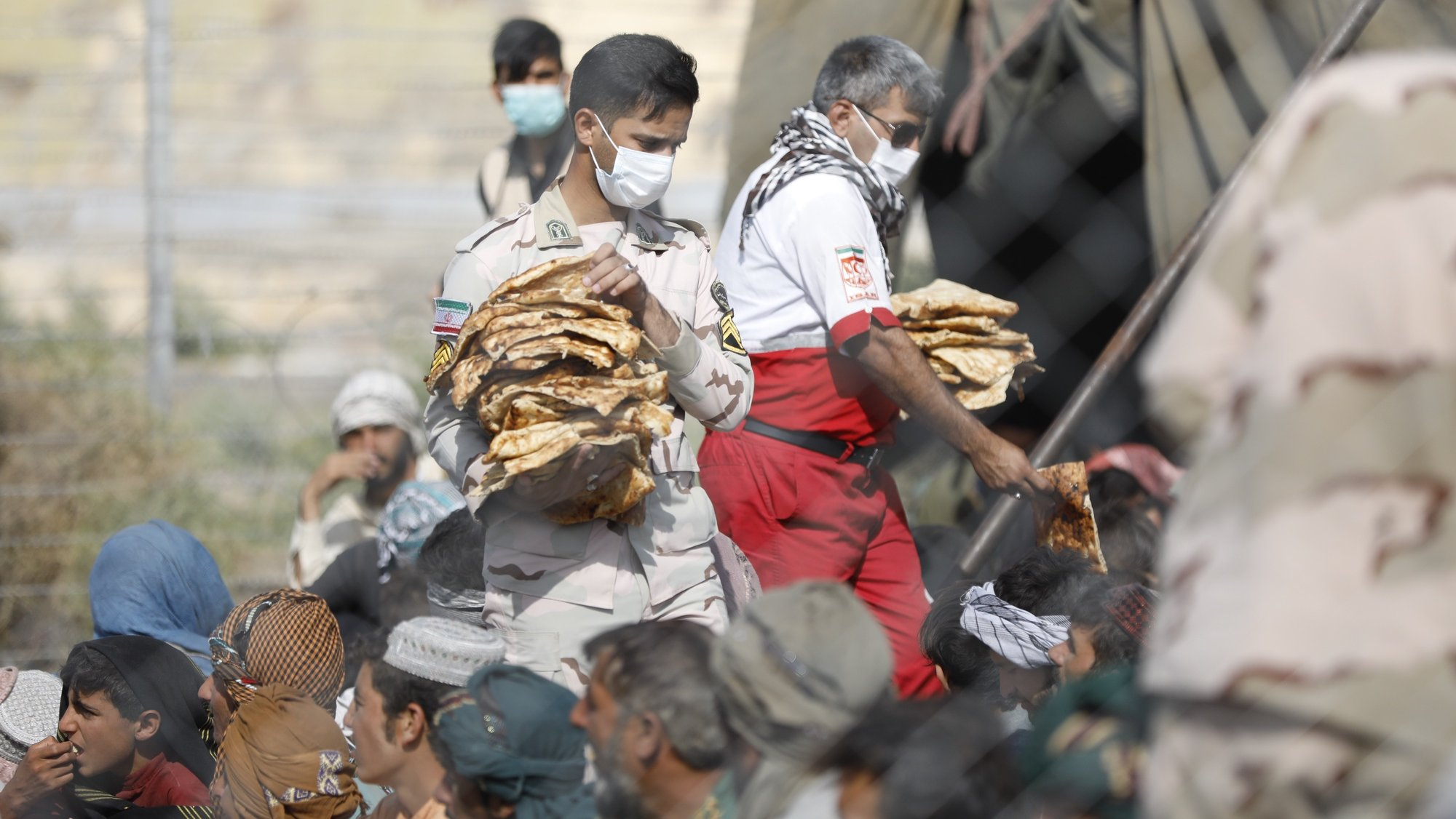 epa09420825 A handout photo made available by Iranian Red Crescent shows an Iranian soldier distributes foods among Afghan Afghan refugee gather in Iran-Afghanistan border in Sistan-Blochestan province, south-eastern Iran, 16 August 2021 (issued 19 August 2021). According to Iranian Red Crescent official website, after Taliban took-over the rule in Afghanistan, some Afghan refugees fled to the Iranian borders hoping to enter to Iran. Reports state refugees were sent back to Afghanistan the next day after getting food and help.  EPA/MOHAMMAD JAVADZADEH HANDOUT  HANDOUT EDITORIAL USE ONLY/NO SALES