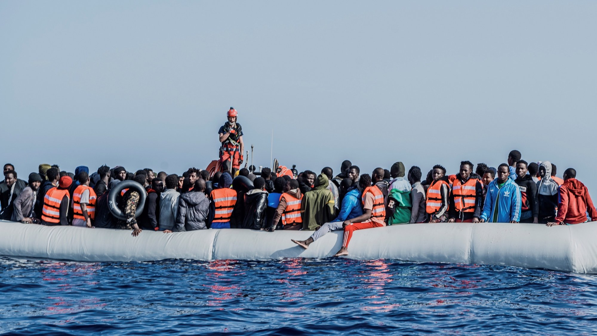 epa09163856 A handout photo made available by SOS Mediterranee show dozens of migrants on board a rubber boat floating in Mediterranean waters off the northeastern coast of Lybia, 27 April 2021. The migrants, including a newborn, 114 minors and seven women, were rescued by the European humanitarian group SOS Mediterranee a rescue charity's ship Ocean Viking.  EPA/Flavio Gasperini / SOS MEDITERRANE / HANDOUT  MANDATORY CREDIT HANDOUT EDITORIAL USE ONLY/NO SALES