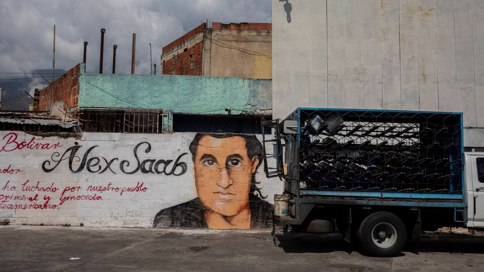 epa09030459 A small truck passes by a graffiti with the image of Alex Saab's face in Caracas, Venezuela, 22 February 2021. Chavista supporters have painted murals in the Venezuelan capital to show their support and request the release of Alex Saab, a Colombian businessman detained in Cape Verde and whom the United States is asking for extradition by accusing him of being a front man for the president of Venezuela, Nicolas Maduro.  EPA/Rayner Pena