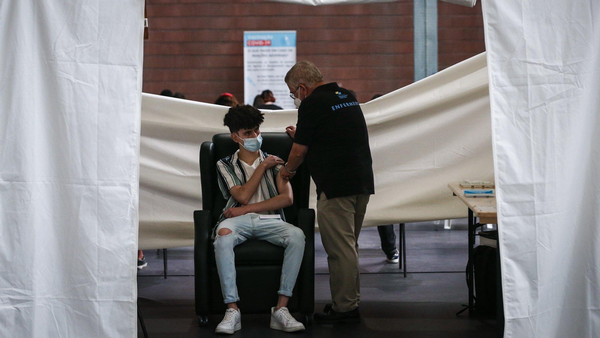 Um adolescente é vacinado contra o Covid-19 durante o fim de semana de vacinação de jovens de 16 e 17 anos, no Pavilhão António Feliciano Bastos, em Loures , 14 de agosto de 2021.  RODRIGO ANTUNES/LUSA