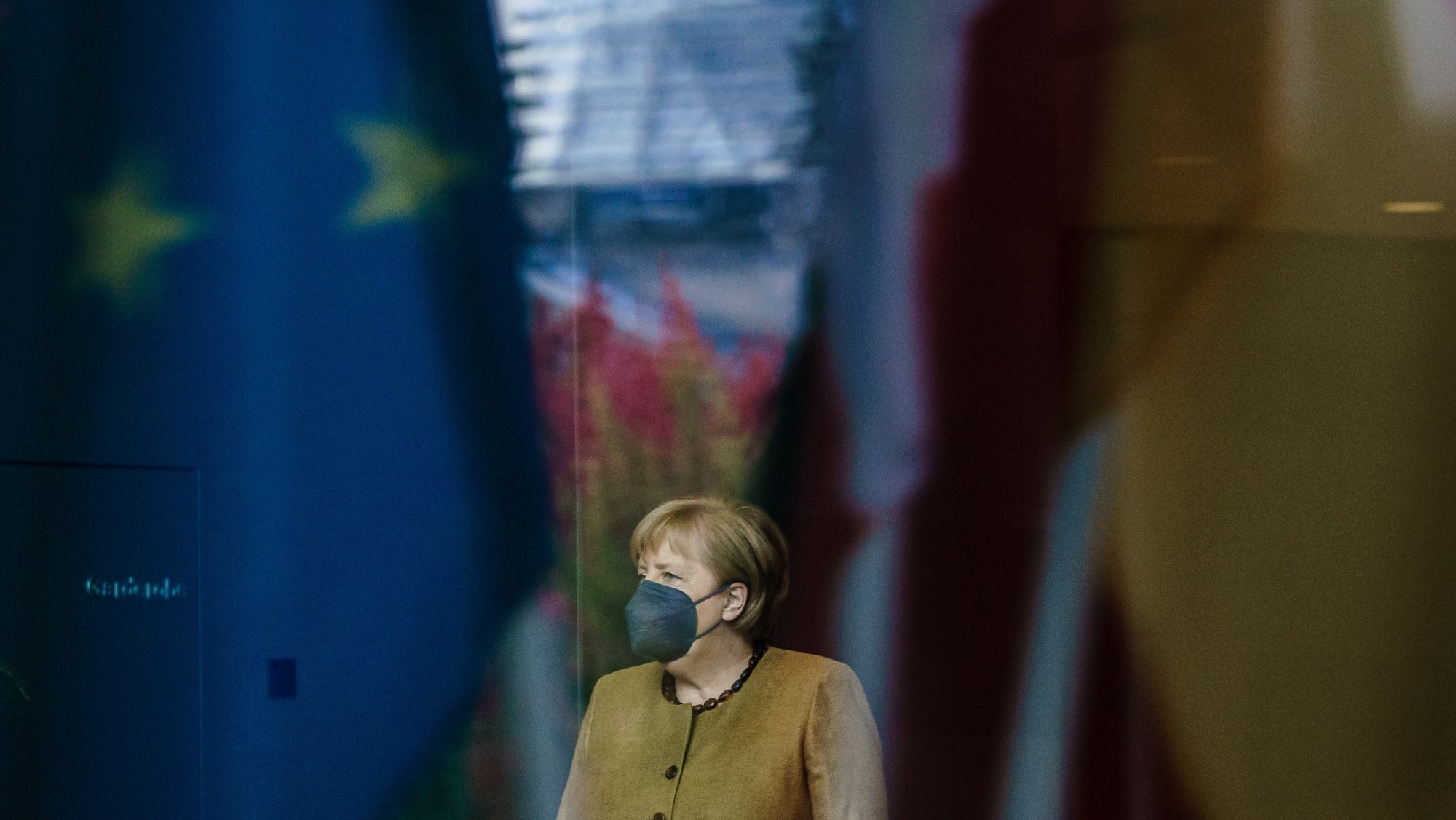 epa09519736 German Chancellor Angela Merkel, seen behind reflections of flags and the dome of the German Parliament 'Bundestag', waits for the arrival of Italian President Sergio Mattarella at the chancellery in Berlin, Germany, 12 October 2021. Merkel and Mattarella meet for bilateral talks. The Italian president is on an official visit to Berlin.  EPA/CLEMENS BILAN