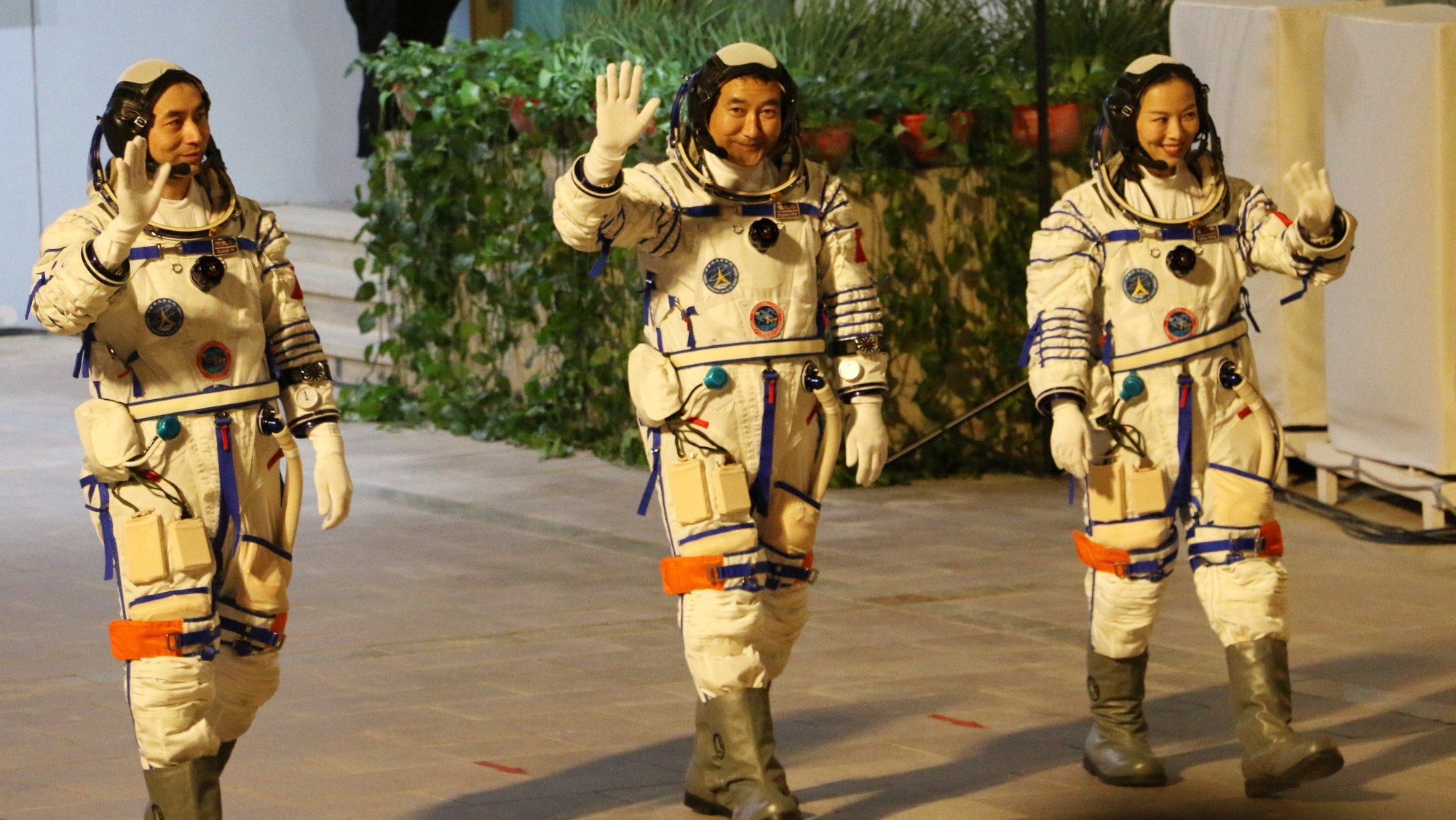 epa09525897 (L-R) Astronauts Ye Guangfu, Zhai Zhigang, and Wang Yaping, greet the crowd before their departure to Tiangong space station at the Jiuquan Satellite Launch Center in northwest China, 15 October 2021. The trio will stay in orbit for six months, a regular duration for future Tianhe space station visitors.  EPA/LIU HUAIYU CHINA OUT