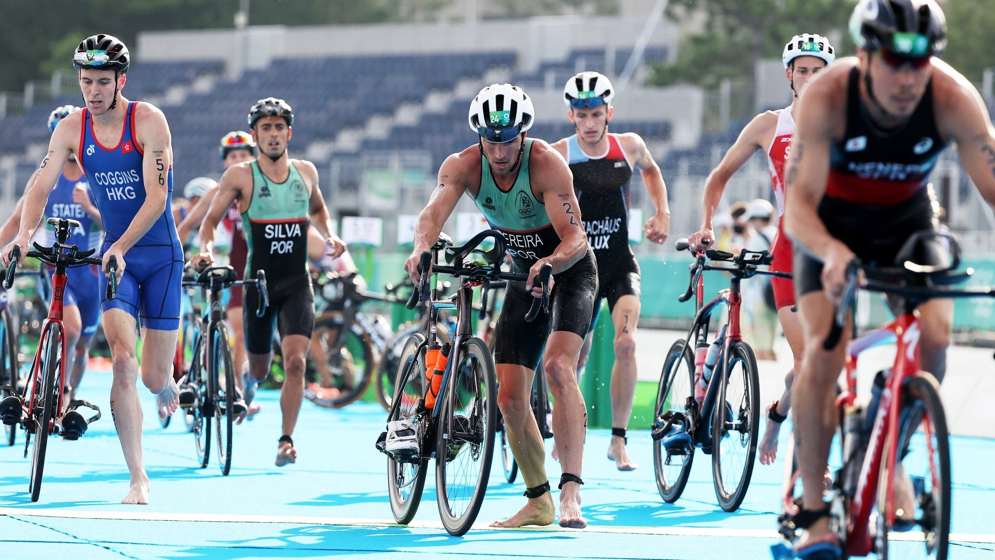 epa09365641 Joao Pereira (C) of Portugal gets on his bike for the cycling section of the Men's Triathlon race of the Tokyo 2020 Olympic Games at the Odaiba Marine Park in Tokyo, Japan, 26 July 2021.  EPA/WU HONG