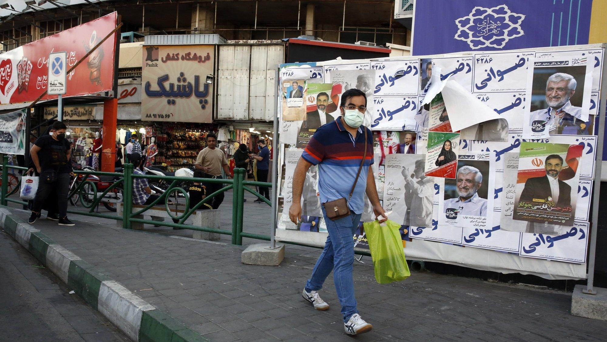 epa09274024 An Iranian man walks past elections billboard in a street in Tehran, Iran, 15 June 2021. Iranians will vote in a presidential election on 18 June 2021.  EPA/ABEDIN TAHERKENAREH