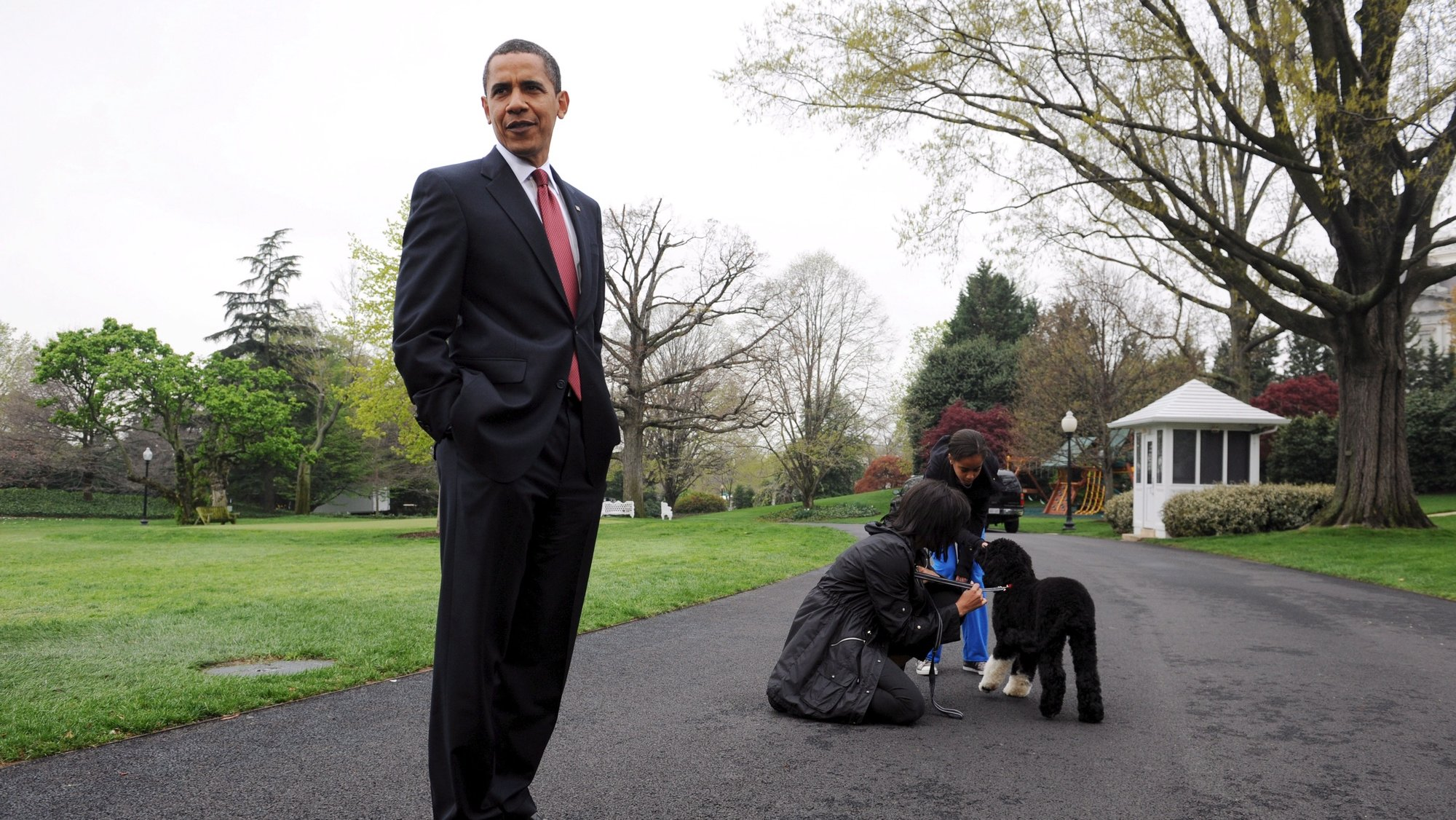 epa09186447 (FILE) - US President Barack Obama (L), speaks to members of the press while First Lady Michelle Obama (back L) and one of their daughters Malia (back R) play with the new White House dog Bo, a six-month-old black-and-white Portuguese water dog, at the South Lawn of the White House in Washington, DC, USA, 14 April 2009 (Reissued 08 May 2021). Former US President Barack Obama and First Lady Michelle Obama announced on 08 May that their dog Bo has died of cancer.  EPA/MICHAEL REYNOLDS