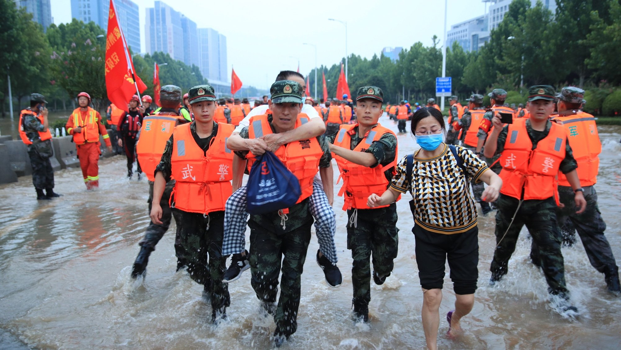 epa09358203 Rescuers evacuate people from a hospital where about 3,000 people were trapped by the flood in Zhengzhou, central China's Henan province, 22 July 2021. Thirty-three people were found dead in the flooding, and eight more are missing.  EPA/STRINGER CHINA OUT