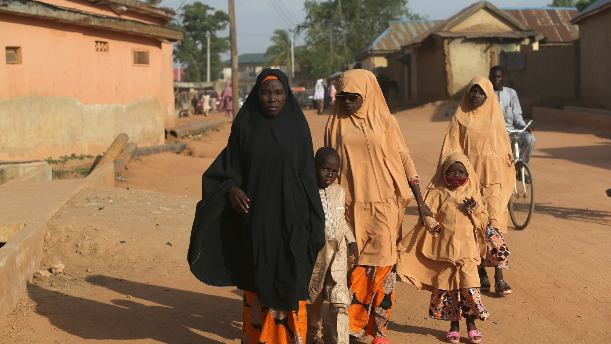 epa09200616 A Muslim woman walks along a road with her children after attending the Jumat prayer at the Zaria central mosque in northern Nigeria 14 May 2021. Muslims around the world are celebrating Eid al-Fitr, the three day festival marking the end of the Muslim holy fasting month of Ramadan. Eid al-Fitr is one of the two major holidays in Islam.  EPA/AKINTUNDE AKINLEYE