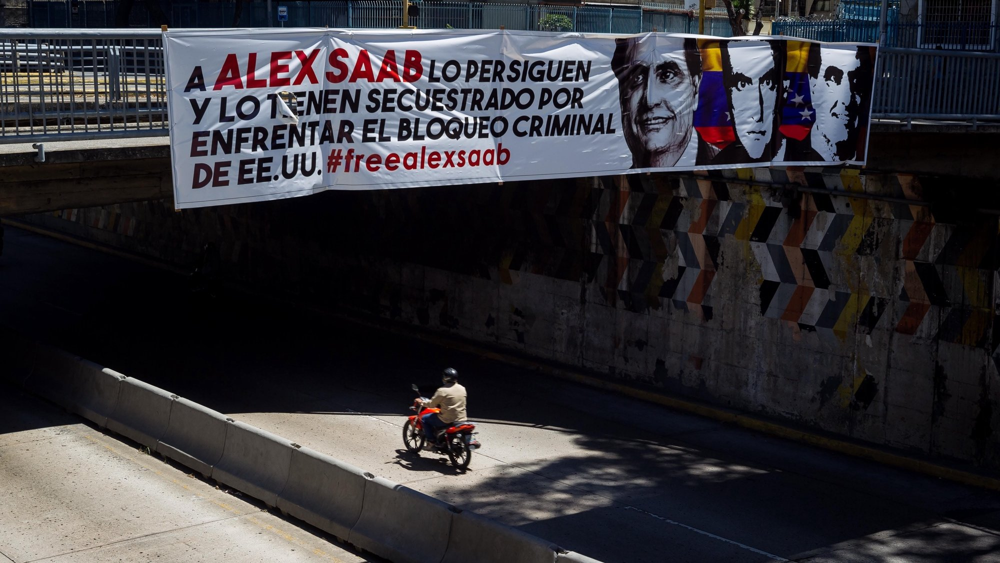 epa09024180 A banner in support of Alex Saab hangs from a bridge in Caracas, Venezuela, 19 February 2021. Venezuelan diplomat Alex Saab was arrested in Cape Verde in June 2020 at the request of the USA for alleged financial crimes, he was later placed under house arrest in January 2021.  EPA/Miguel Gutiérrez