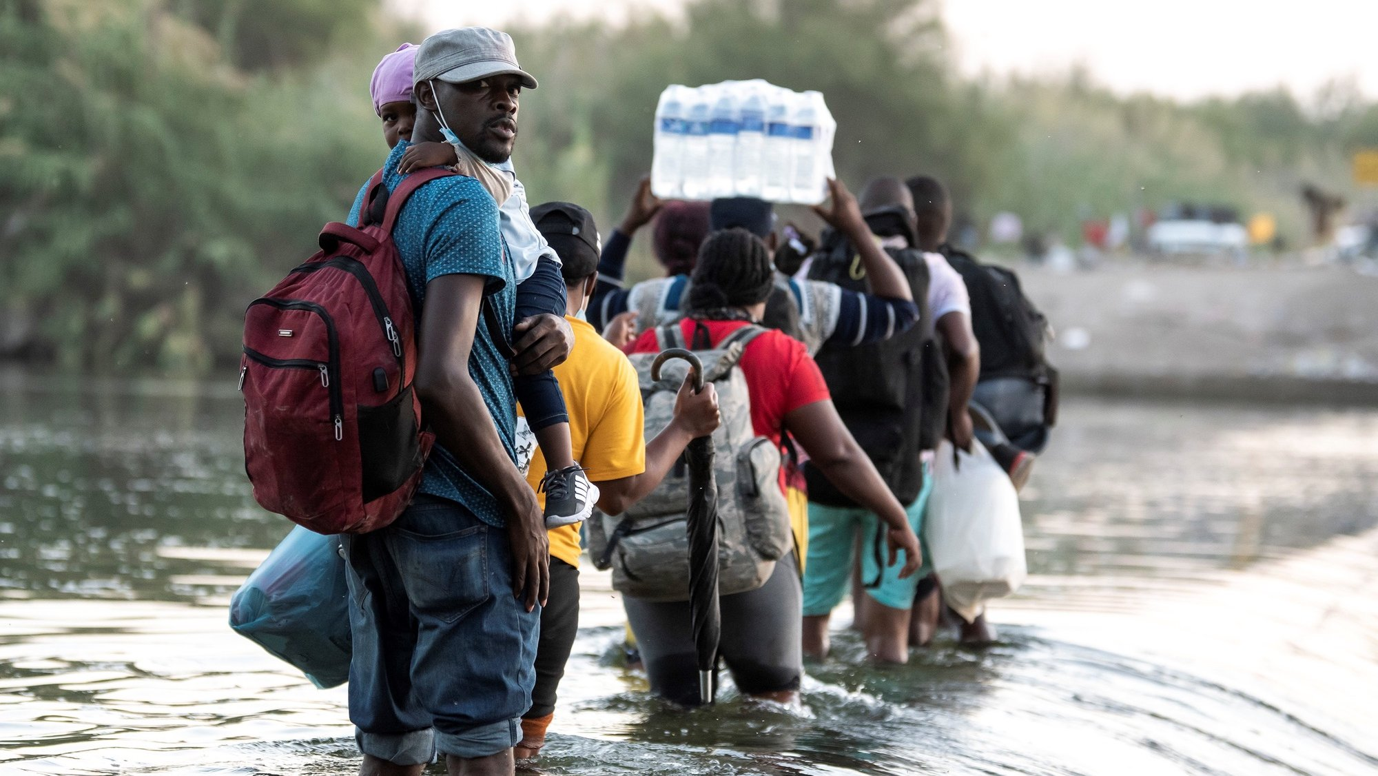 epa09475512 A group of Haitian migrants begin to cross the Rio Grande, on the border of Ciudad Acuna, Mexico, 18 September 2021. More than 10,000 migrants have arrived in the border cities of Del Rio Texas in the United States and Ciudad Acuna in Mexico in recent days and are waiting under the International Bridge for the asylum application to be processed by the United States authorities.  EPA/Miguel Sierra
