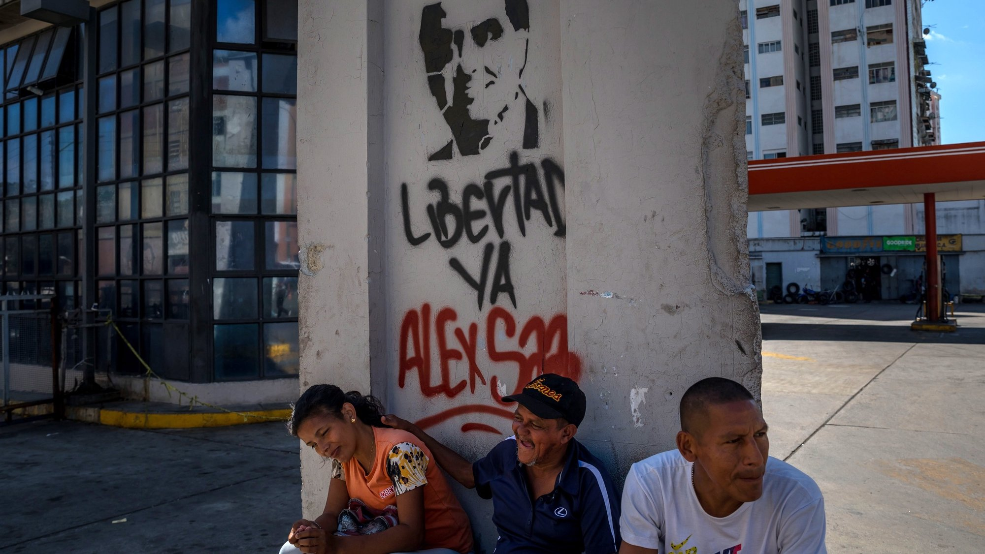 epa08990282 Several people is sitting next to a wall with graffiti demanding the release of Alex Saab, in Caracas, Venezuela, 05 February 2021. The Court of Justice of the Economic Community of West African States (ECOWAS) held on 05 February a hearing on the extradition case of Álex Saab, alleged front man of the President of Venezuela, Nicolás Maduro, arrested in Cape Verde and claimed by the US for alleged money laundering.  EPA/MIGUEL GUTIERREZ