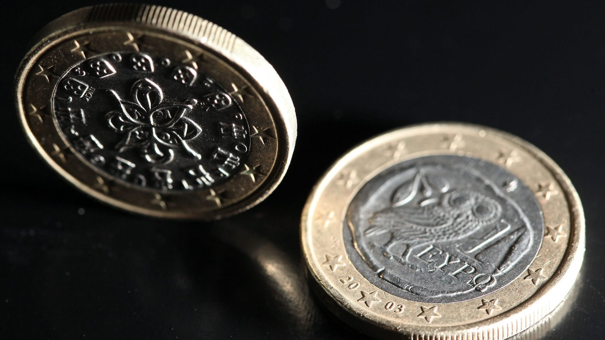 epa02736411 An illustration photo shows two 1-Euro coins with a national Portuguese (L) and a national Greek backside (R), arranged on a table in Cologne, Germany, 16 May 2011. European Union Economy Commissioner Olli Rehn criticized Greece on 16 May for its slow pace of reform, hours before eurozone finance ministers were due to discuss the country's debt problems at a meeting in Brussels. Rehn also called upon Germany to support the 78-billion-euro rescue package for Portugal, which the EU finance ministers were due to decide about at their meeting in Brussels.  EPA/OLIVER BERG