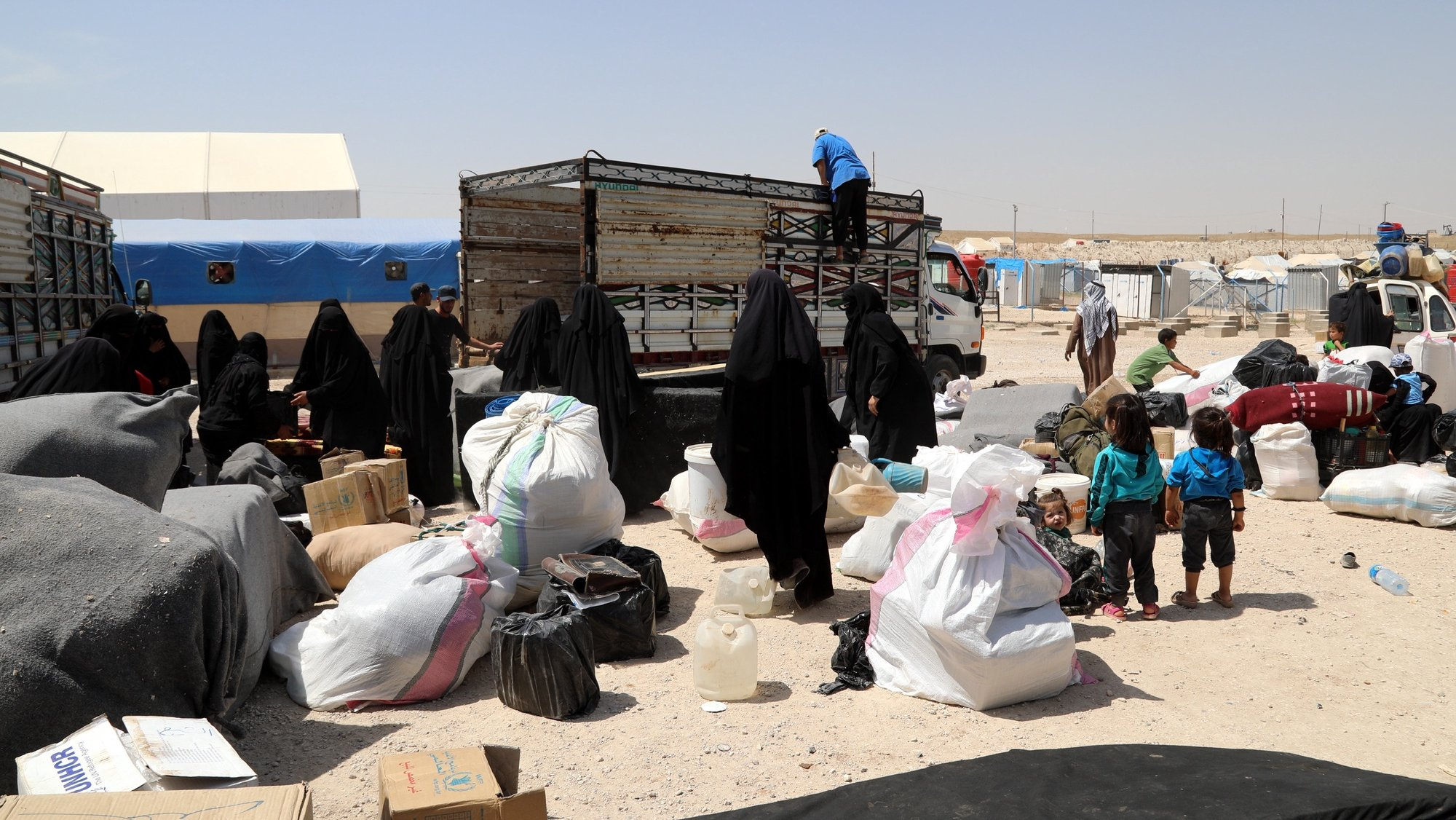 epa07623494 Wives of Islamic state fighters (IS) load their belongings into a truck upon their deportation from the al-Hol camp for refugees in al-Hasakah governorate in northeastern Syria on 03 June 2019 (issued 04 June 2019).  According to media reports, the Kurdish authorities in northeast Syria are handing over 800 women and children all of them Syrian, including relatives of Islamic state fighters, to their families in the first such transfer from an overcrowded camp.  EPA/AHMED MARDNLI