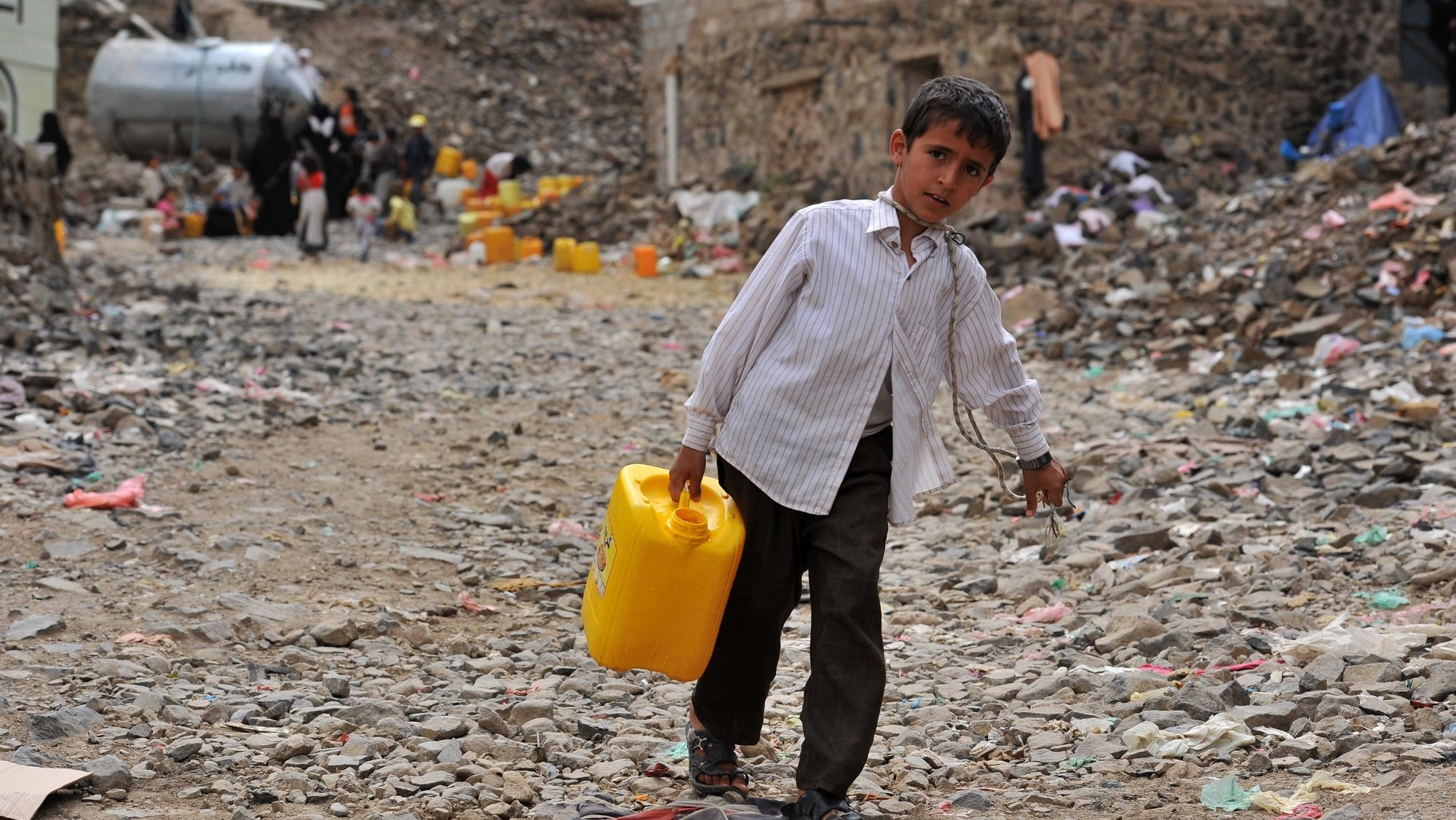 epa03792656 A Yemeni boy holds a jerry can after filling with water from a philanthropist-provided tap at a slum in Sana'a, Yemen, 18 July 2013. Reports state the United Nations has appealed to the international community to provide 702 million US dollar to help 7.7 million of the most vulnerable Yemenis gain access to food, clean water, health care and other vital services. Half of Yemen's 24 million people are in need of assistance, as the impoverished Arab country is facing a worsening humanitarian situation during a political transitional period.  EPA/YAHYA ARHAB