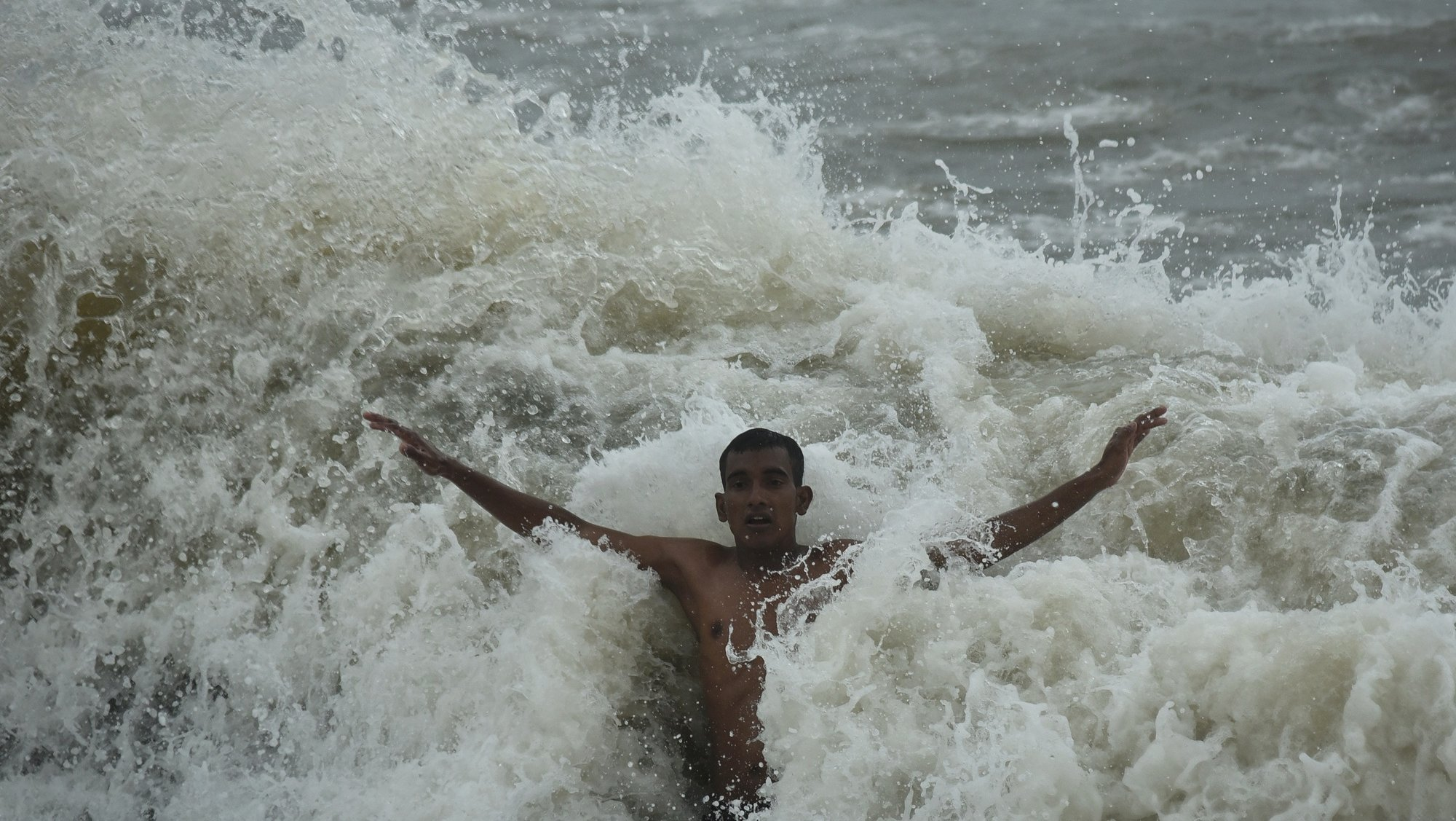 epa09356753 A youth gets splashed by a huge wave while swimming at Foreshore Estate beach in Chennai, India. 21 July 2021.  EPA/IDREES MOHAMMED