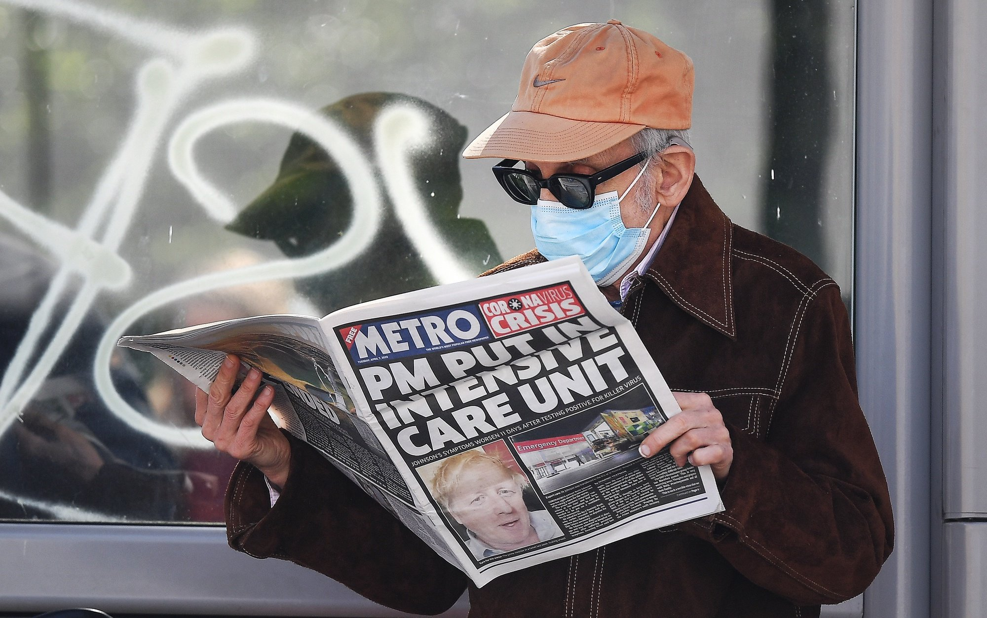 epa08347768 A man wearing a protective mask reads the news about British Prime Minister Boris Johnson's condition outside St.Thomas' Hospital in London, Britain, 07 April, 2020.  According to a statement by his office, British Prime Minister Boris Johnson was admitted into St. Thomas' Intensive Care Unit (ICU) on the evening of 06 April – 11 days after first having tested positive for the pandemic COVID-19 disease caused by the SARS-CoV-2 coronavirus – due to a worsening of his symptoms. First Secretary of State Dominic Raab, who also serves as Secretary of State for Foreign and Commonwealth Affairs, will be deputizing for Johnson when needed, the statement added.  EPA/ANDY RAIN
