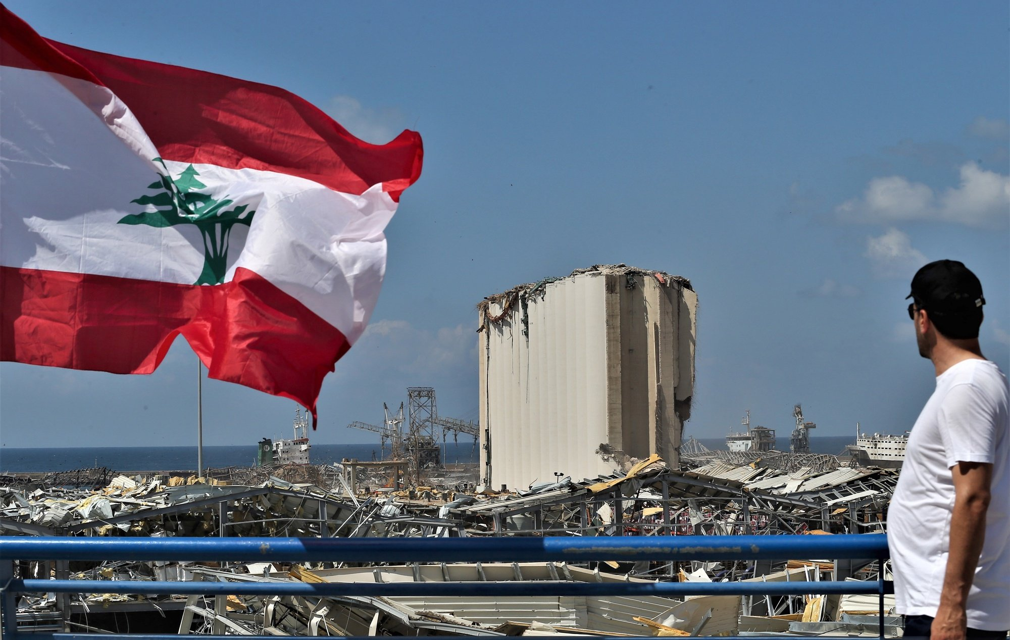 epaselect epa08594054 A man stands next to a Lebanese flag on a bridge overlooking the damaged Beirut port and grain silos, in Beirut, Lebanon, 09 August 2020. Large numbers of families flocked to stand on the bridge overlooking the site of the explosion in the port to look closely and take pictures. Lebanese Health Ministry said at least 160 people were killed, and more than 6000 injured in the Beirut blast that devastated the port area on 04 August and believed to have been caused by an estimated 2,750 tons of ammonium nitrate stored in a warehouse.  EPA/NABIL MOUNZER