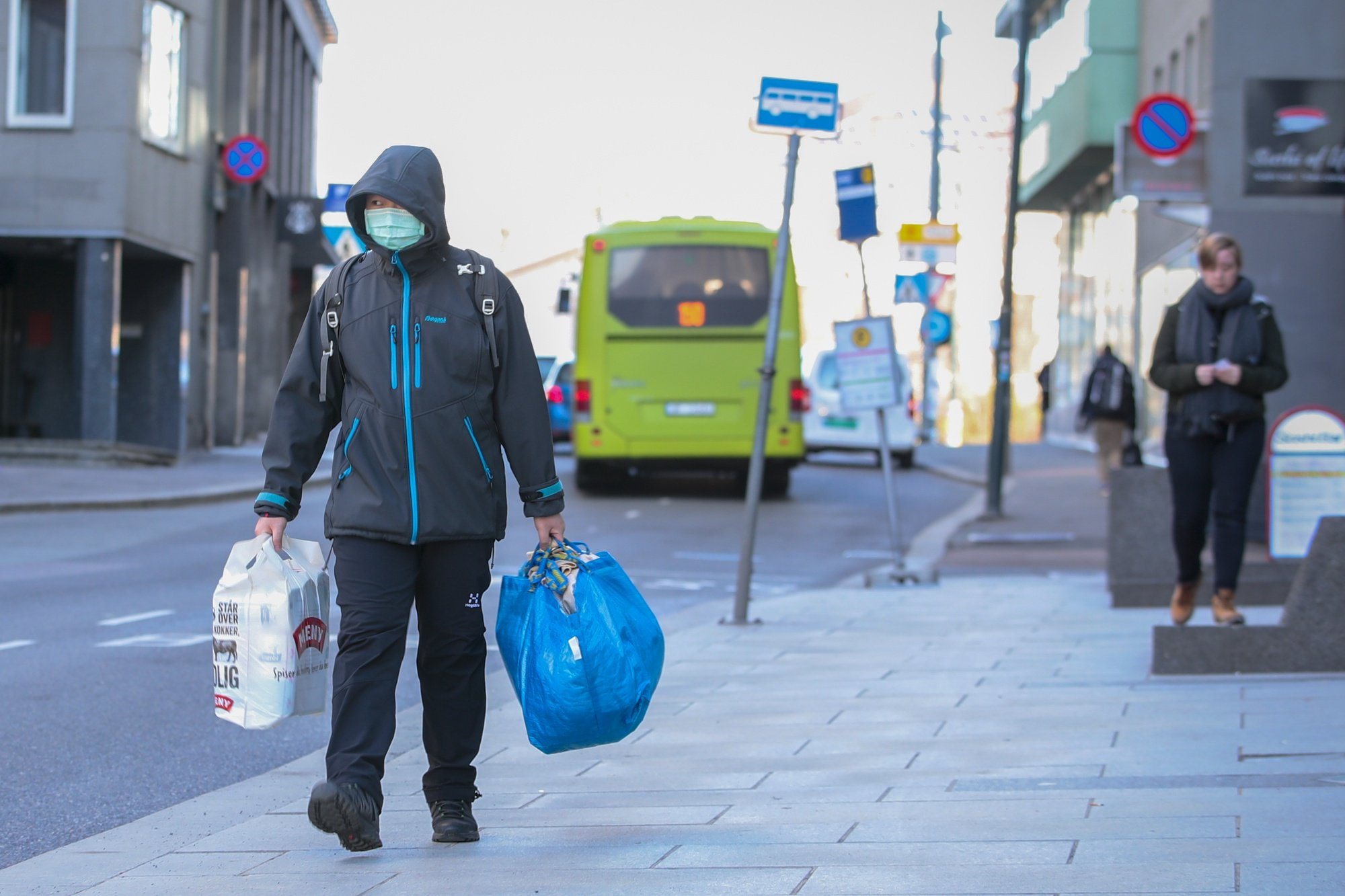 epa08291576 A man protecting himself with a mask carries shopping bags on a street of Oslo, Norway, 13 March 2020. Due to coronavirus COVID-19 outbreak it is relatively quiet in the streets of Norway's capital.  EPA/HAKON MOSVOLD LARSEN  NORWAY OUT