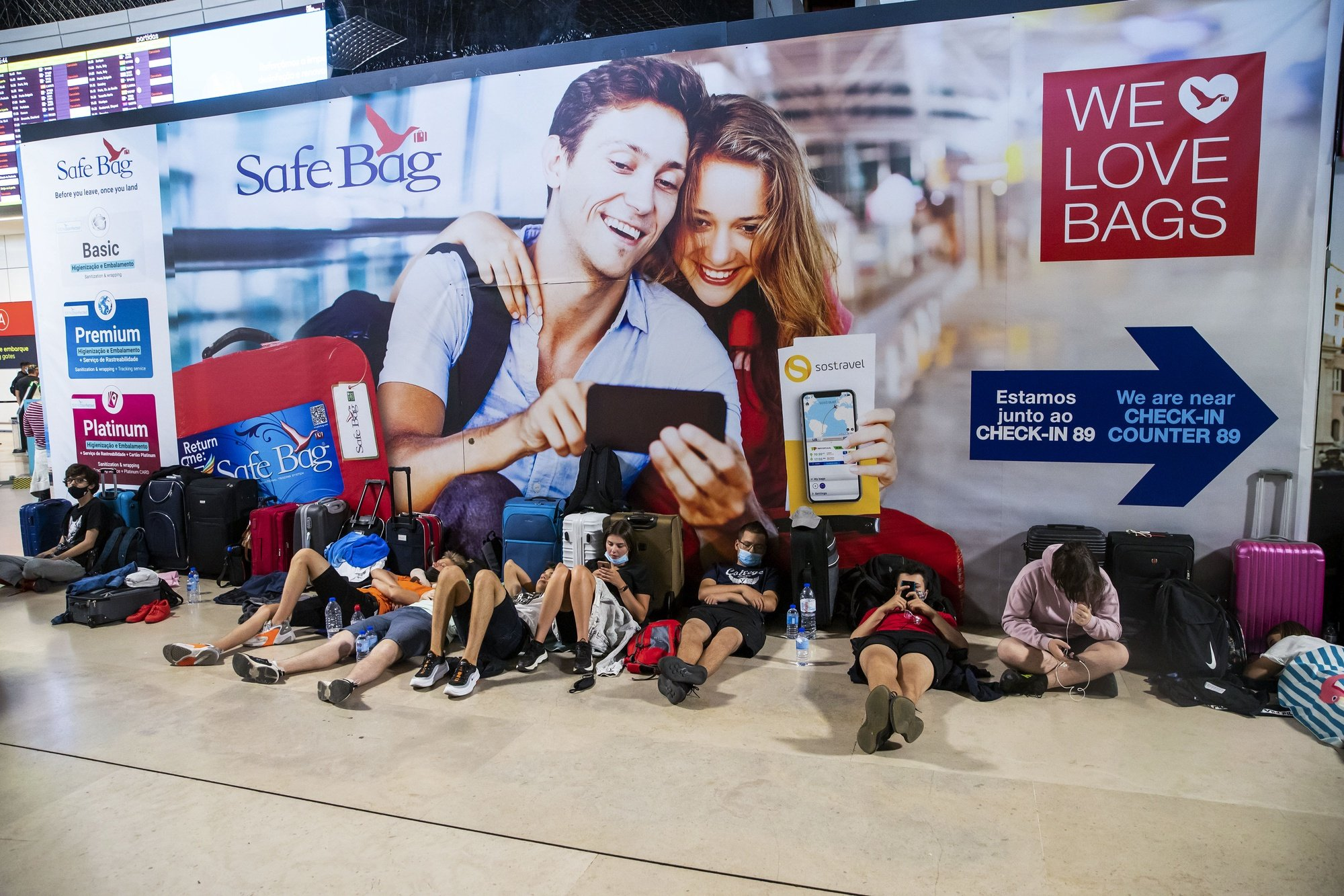 Passengers lay on the floor as they wait for their flight due to a strike of the handling company, Groundforce, which is causing major disruption in the Lisbon Airport, causing the cancelation of dozens of flights, in Lisbon, Portugal, 17 July 2021. Groundforce workers are protesting against colective dismissal of workers and low salaries. JOSE SENA GOULAO/LUSA