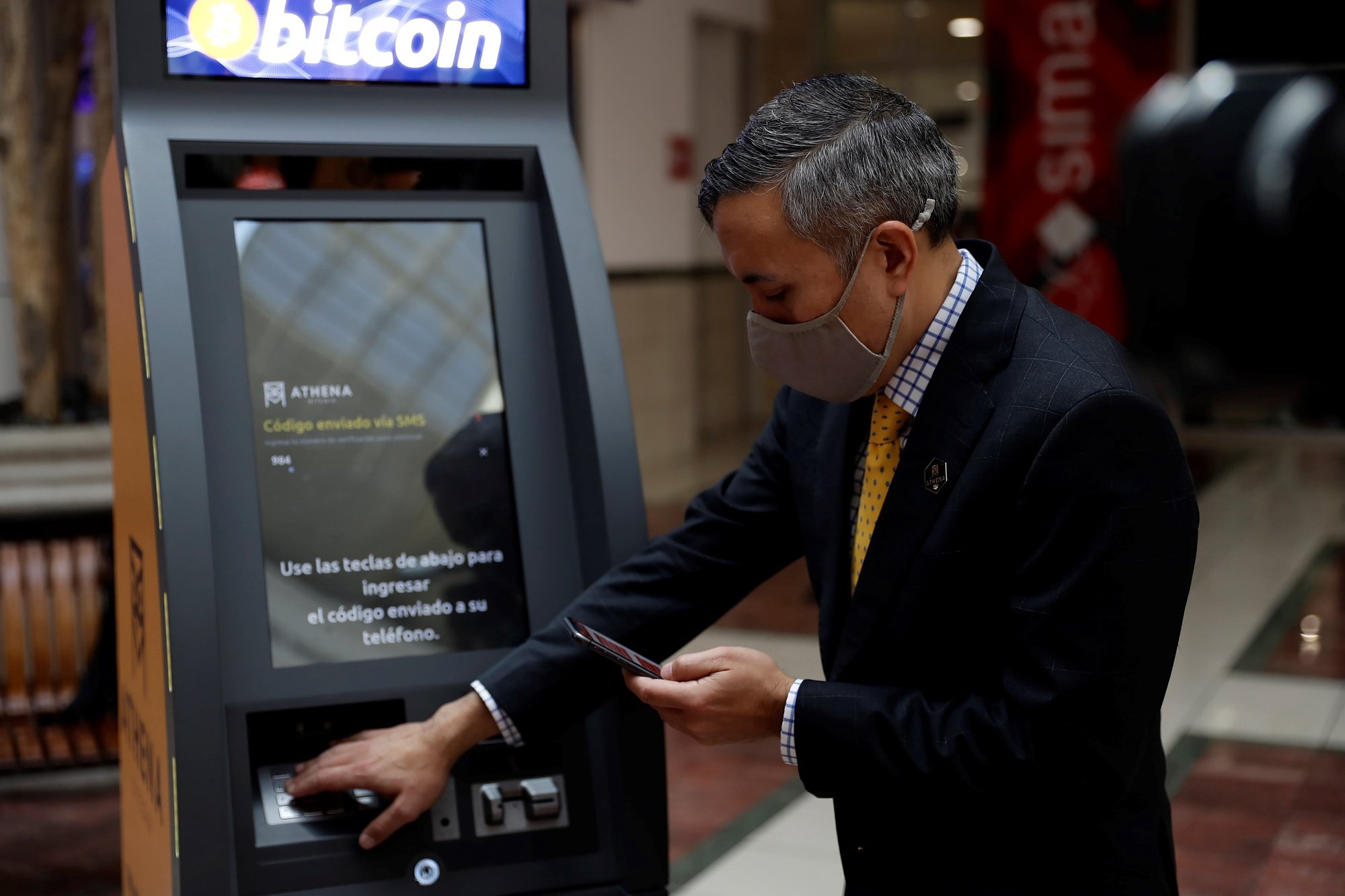 epa09299465 Eric Gravengaard, CEO and founder of the Anthena Bitcoin company, performs an operation at the new ATM for bitcoin transactions, in a shopping center in San Salvador, El Salvador, 24 June 2021. The US company Athena Bitcoin began the process of installing ATMs in El Salvador to carry out different operations of the cryptocurrency bitcoin. The ATM, which is the second in the Central American country after the one installed more than a year ago in the El Zonte tourist beach, is located in a shopping center in the central department of La Libertad.  EPA/Rodrigo Sura
