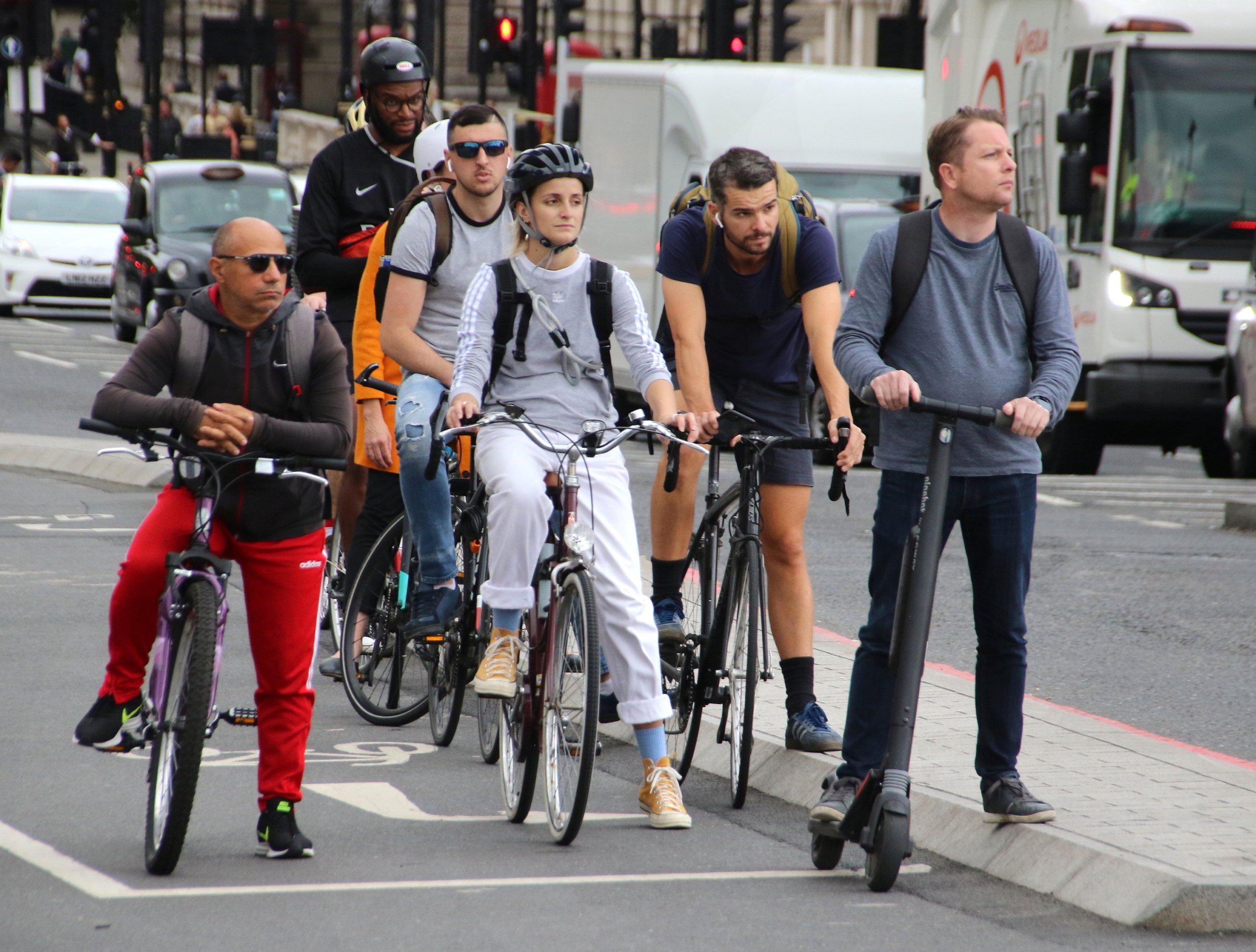 Cyclists and an electric scooter rider wait at traffic