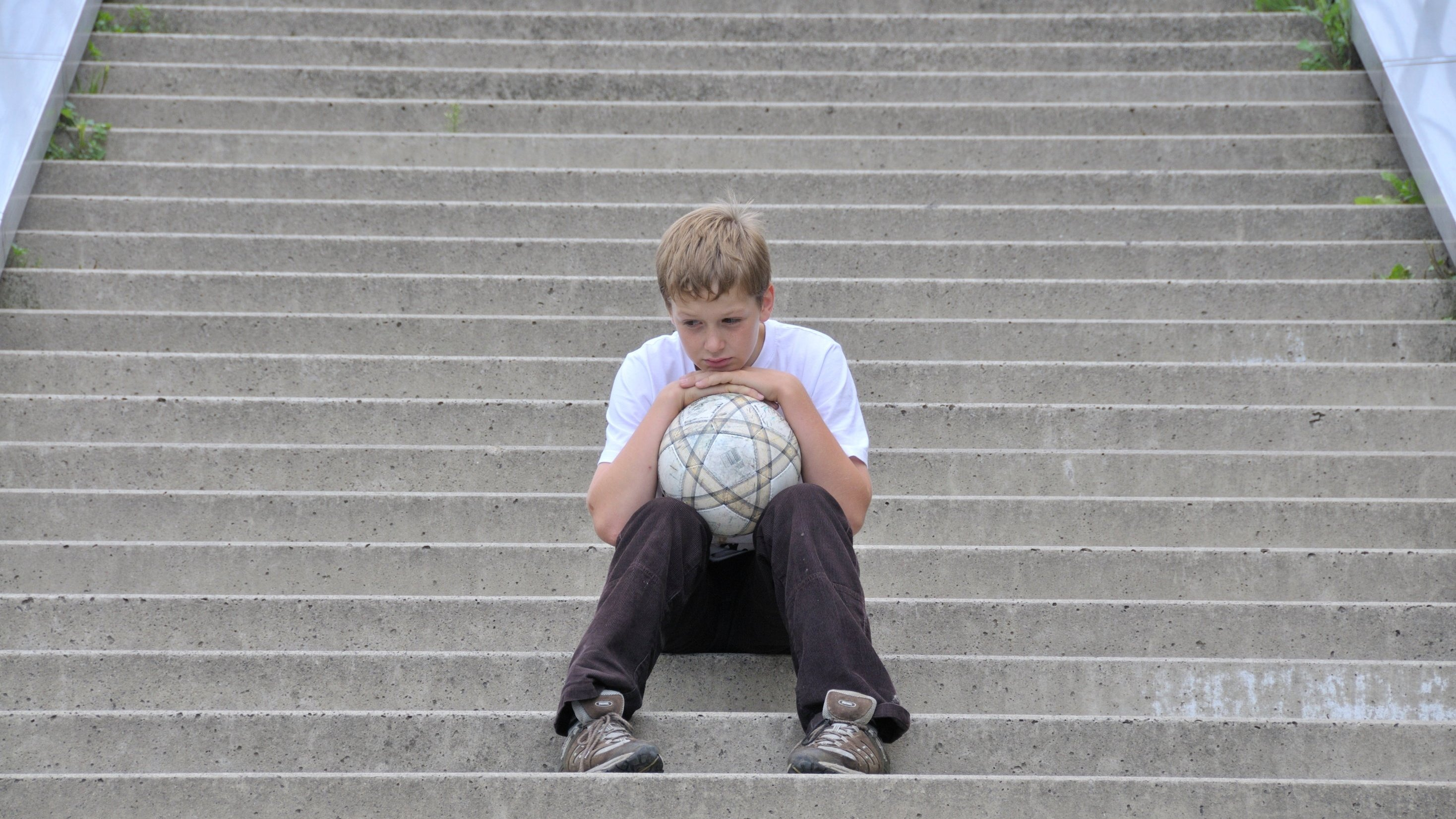 Lonesome boy with football sitting on the stairs - 28.08.2010