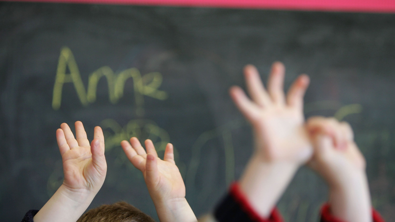 Mãos de crianças numa sala de aula.