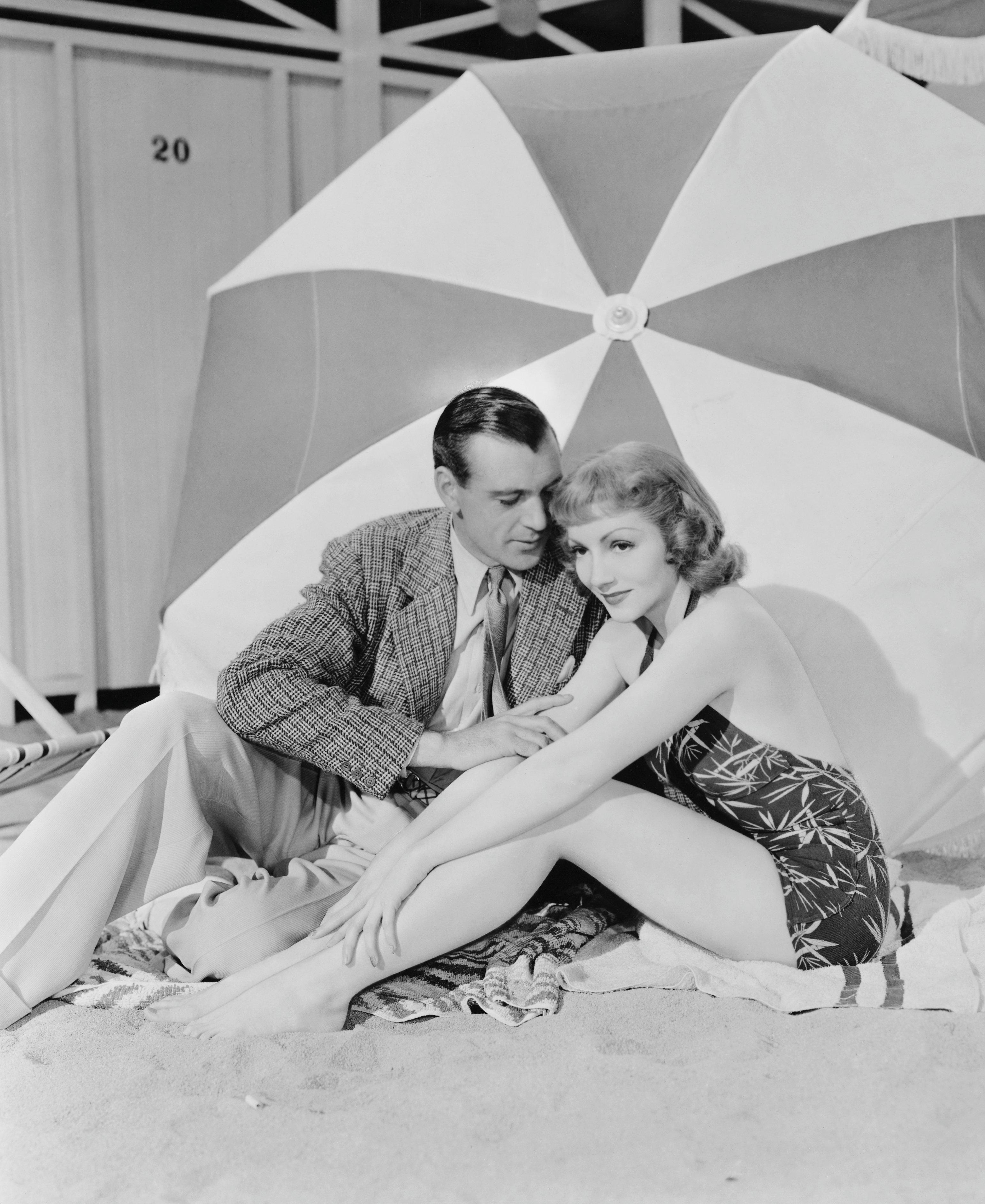 Gary Cooper and Claudette Colbert Seated Under Umbrella