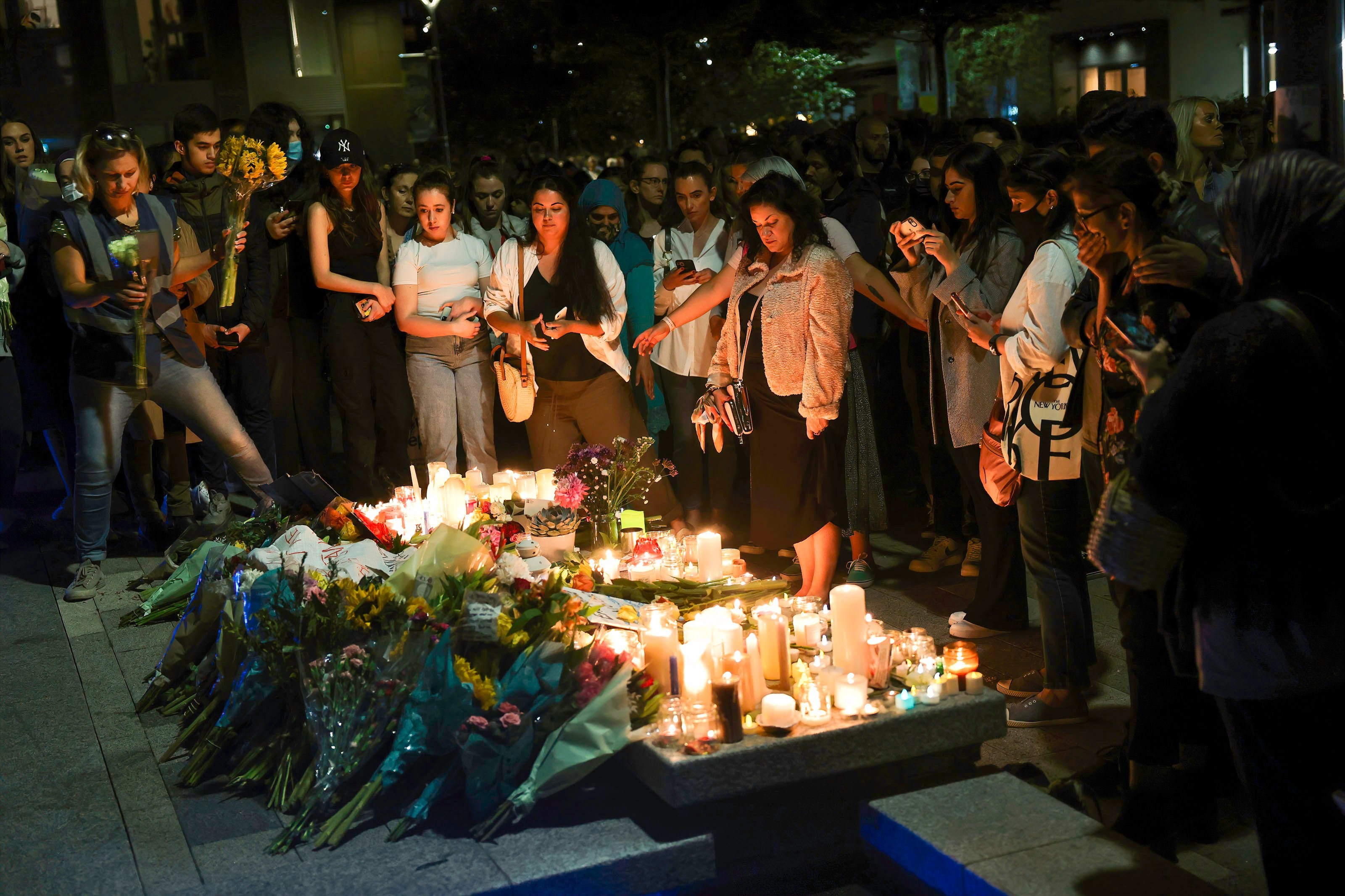 Participants are seen placing lit candles and flowers during