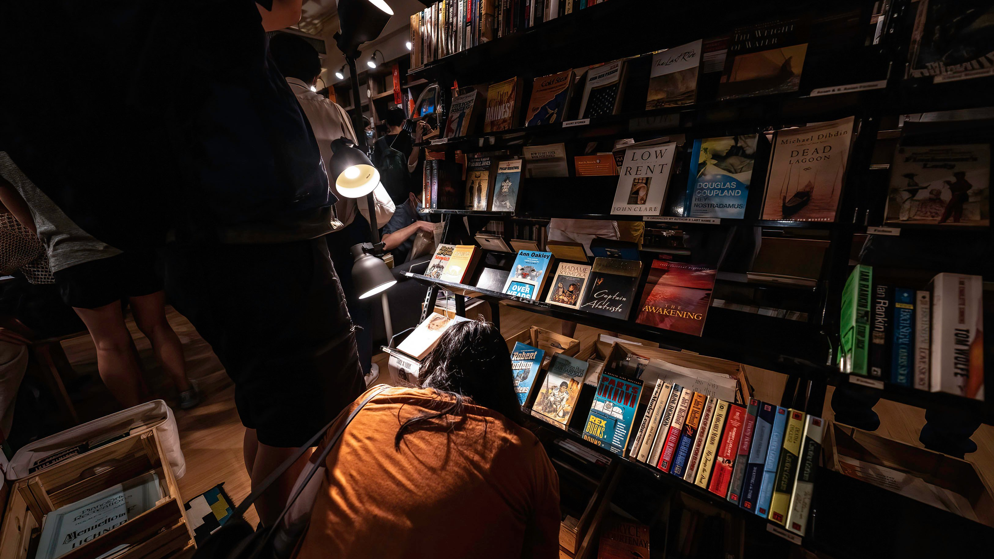 A woman browses the books on a bottom shelf.Crowds of