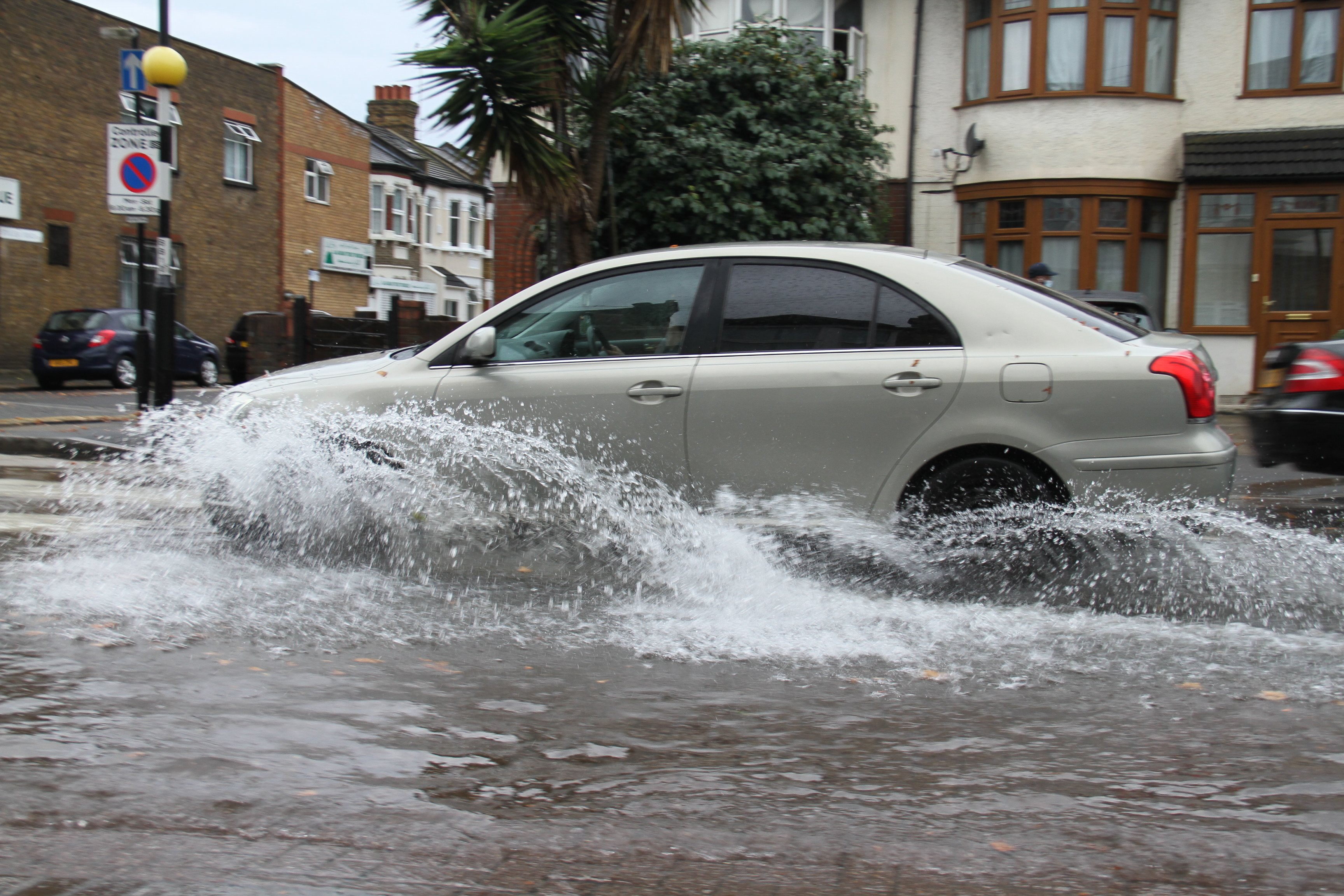 A car drives through flooding on a road in East London