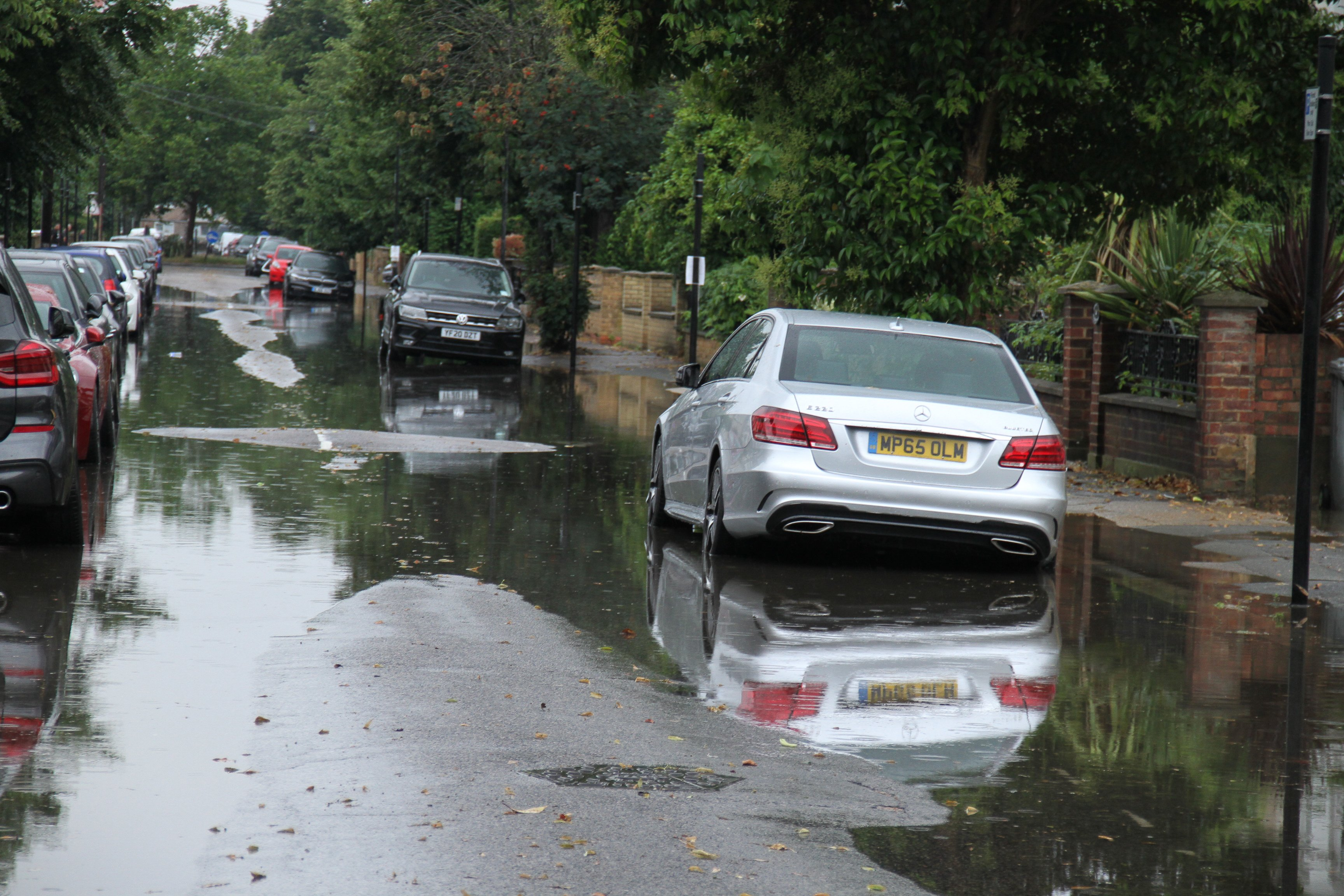 Vehicles seen parked on a flooded street in a suburb in East