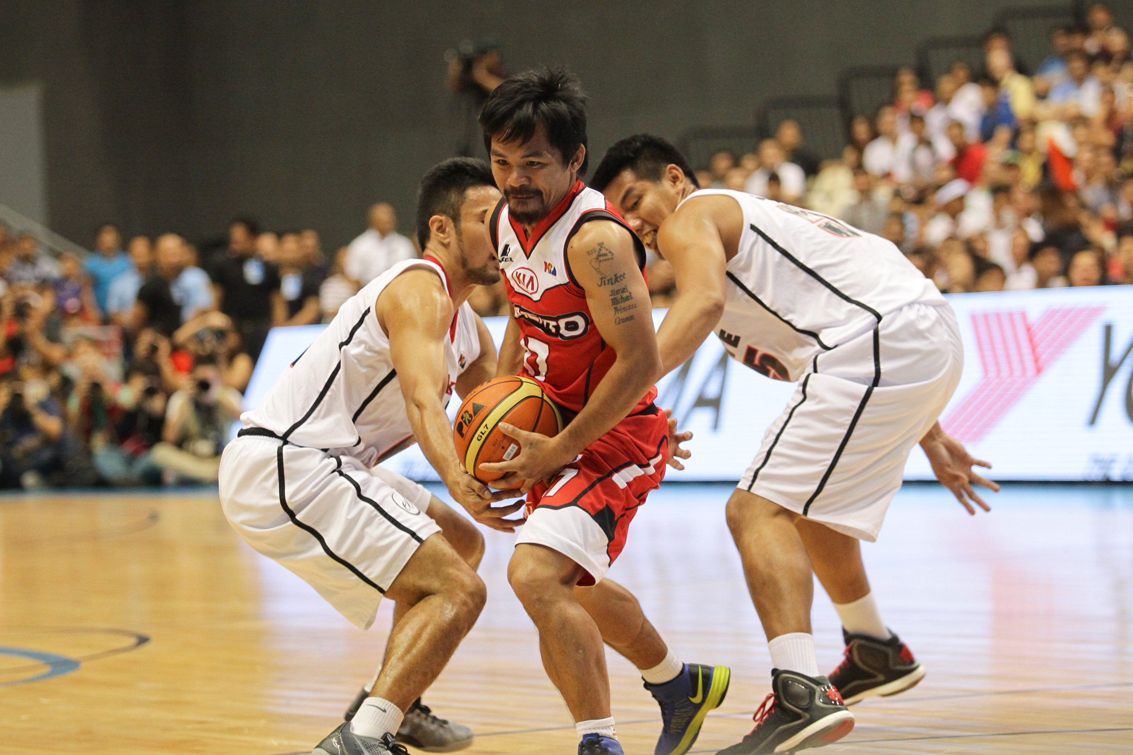 Manny Pacquiao of Kia (C) goes to the basket against