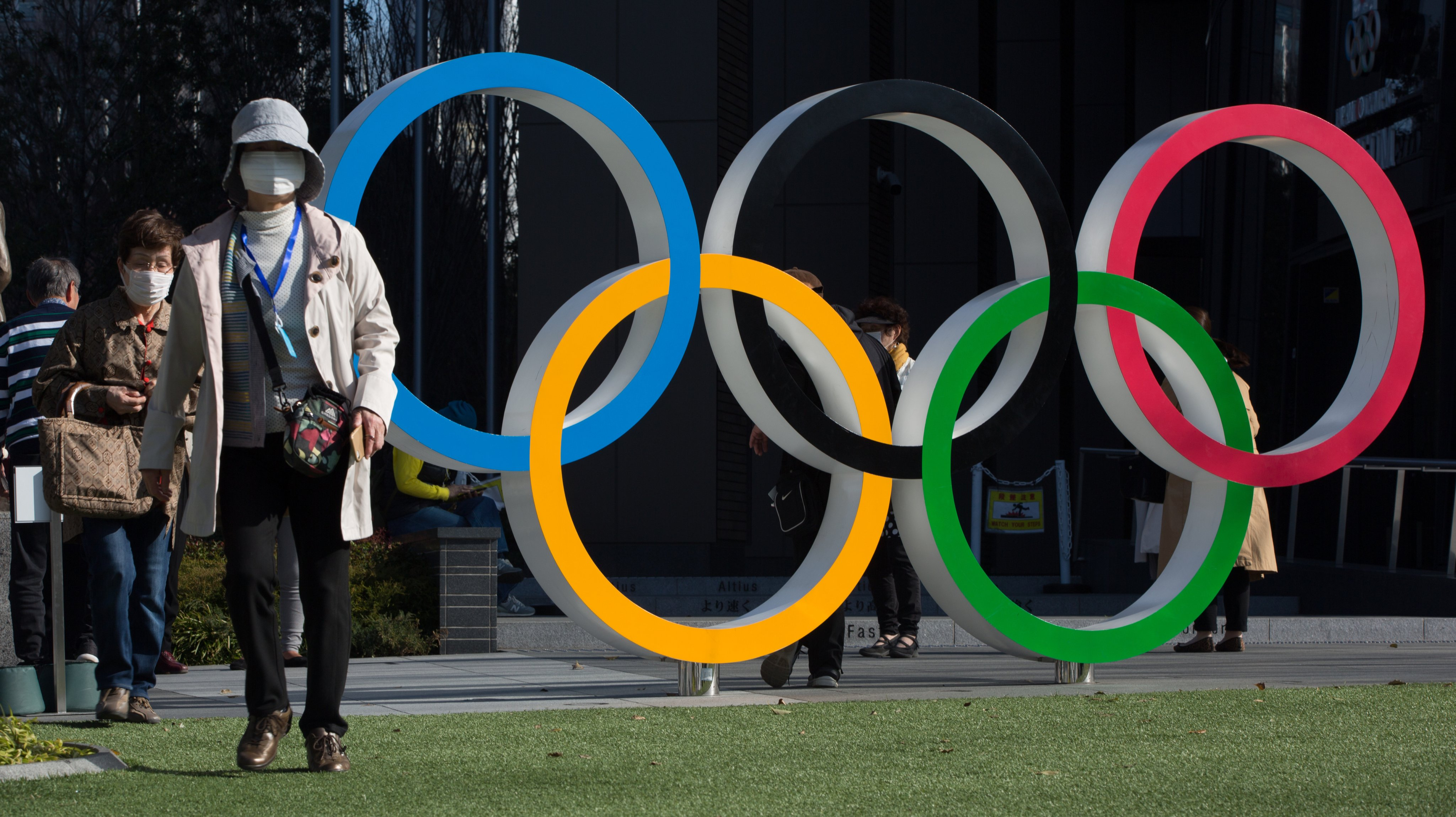 Women with surgical masks walk next to the Olympic Rings in