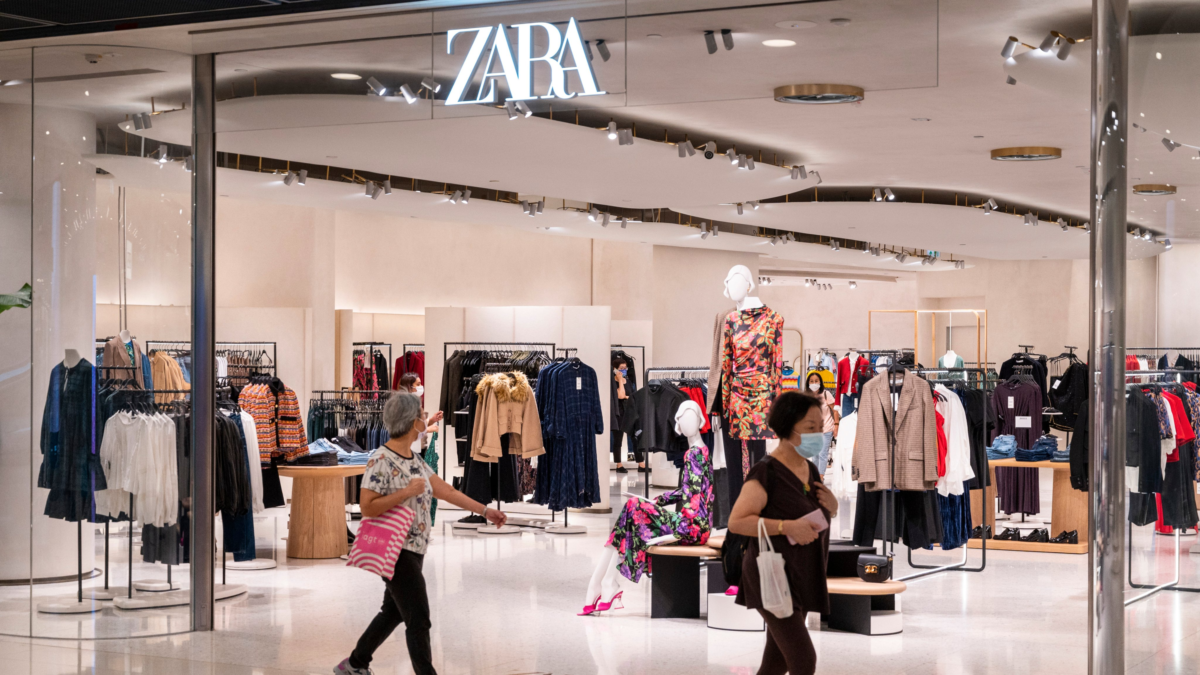Shoppers walk past the Spanish multinational clothing design