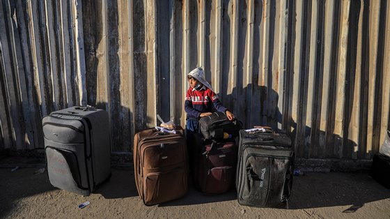 epa08980244 A Palestinian boy waits with his family to cross into Egypt through the Rafah border crossing between Gaza Strip and Egypt after its closure from March 2020 as a precautionary measure against the spread of the coronavirus disease (COVID-19) pandemic, in Rafah, southern Gaza Strip, 01 February 2020. Egyptian Authorities reopened Rafah crossing for four days for the Fifth time since March 2020 for humanitarian cases, including the allowance of crossing the border for people needing medical treatment unavailable in Gaza as well as students enrolled at Egyptian universities and Gazans with jobs abroad.  EPA/MOHAMMED SABER