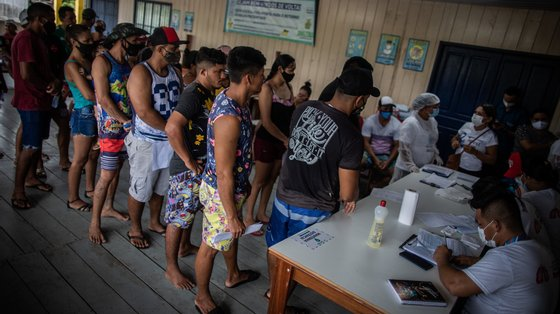 epa09231454 People wait to receive a dose of the AstraZeneca (Vaxzevria) vaccine against COVID-19, in the community of Vila do Cuinha in Anama, Brazil, 27 May 2021. Employees of the Municipal Health Secretariat of Anama arrived in Vila do Cuinha, after a 20-minute boat trip along the Solimoes River from the Anama municipality headquarters, with the aim of vaccinating 190 people, over 18 years of age, with at least the first dose of the COVID-19 immunizer. People received the vaccine at one of the community colleges.  EPA/Raphael Alves