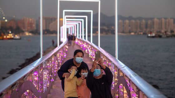 epa08984191 A family takes a selfie on a jetty decorated with lights installed to celebrate the Lunar New Year in Hong Kong, China, 03 February 2021. The Lunar New Year falls on 12 February this year and will celebrate the Year of the Ox, one of the 12 animals of the Chinese Zodiac.  EPA/JEROME FAVRE