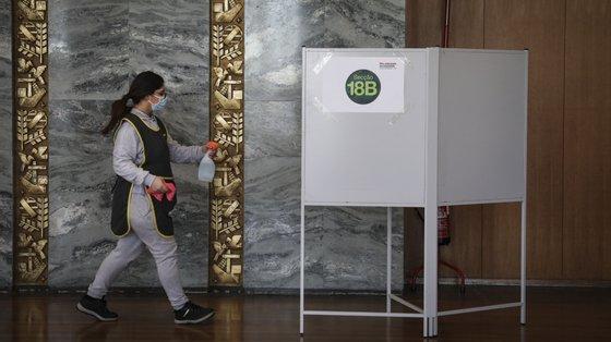 Uma funcionaria da limpeza momentos andes de desinfetar a urna, no dia de voto antecipado nas Eleições Presidenciais de 2021, na Cidade Universitária, em Lisboa, 17 de Janeiro de 2021. RODRIGO ANTUNES/LUSA